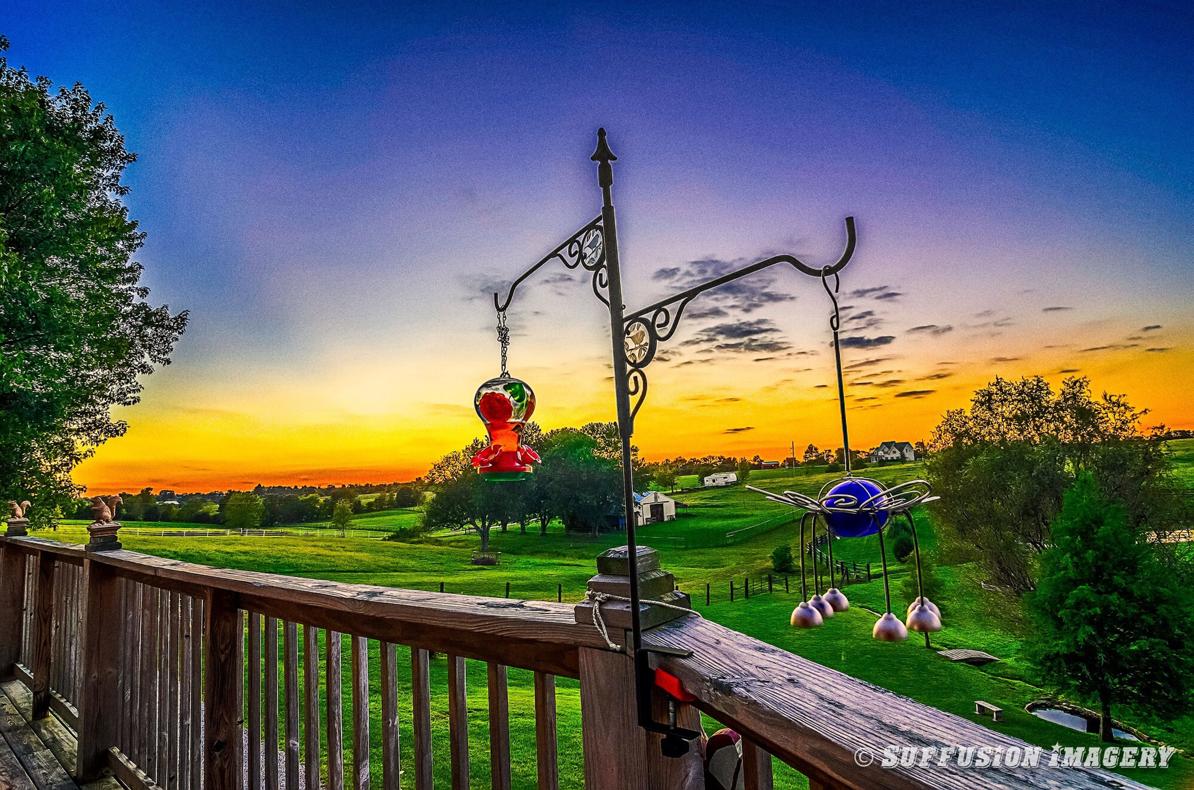 sky, fence, flower, tree, railing, blue, nature, beauty in nature, field, growth, plant, tranquility, sunset, yellow, protection, park - man made space, tranquil scene, scenics, cloud - sky, safety