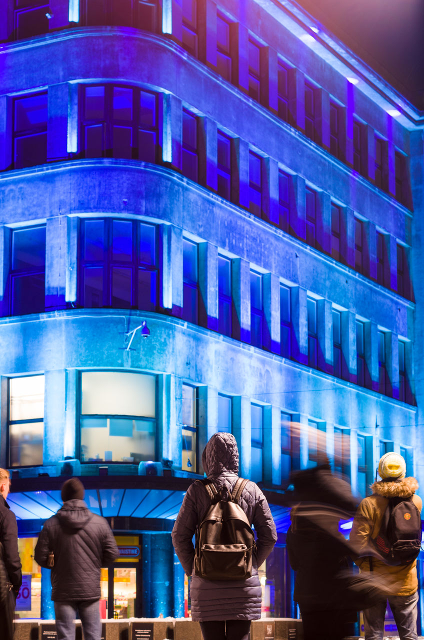 illuminated, architecture, night, real people, building exterior, built structure, walking, women, lifestyles, communication, blurred motion, blue, men, city, outdoors, neon, young adult, adult, people, adults only