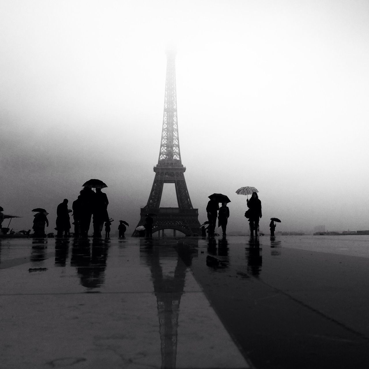 Silhouetted image of tourists at Eiffel Tower in rainy season