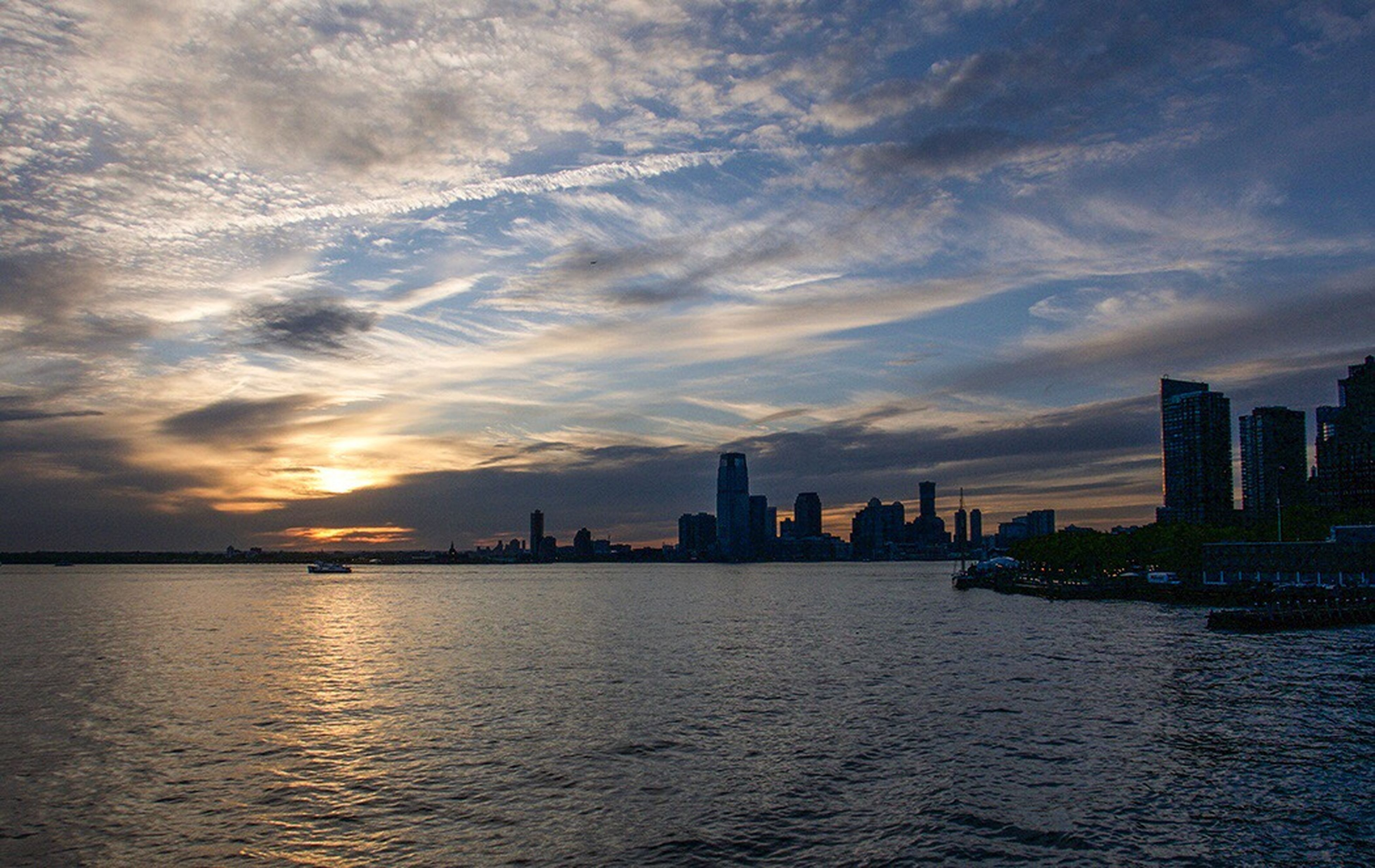 building exterior, sunset, architecture, built structure, sky, water, city, waterfront, cloud - sky, silhouette, sea, cityscape, skyscraper, cloud, urban skyline, scenics, river, tower, rippled, skyline