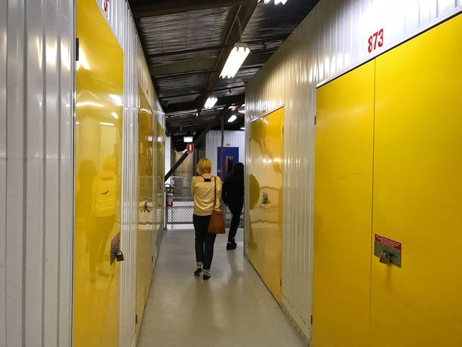 2 Women Blond Blonde Corridor View Corridors  Documenting Space Flourescent Fluorescent Light Illuminated Lights Person Perspective Perspectives Self Storage Signs Storage Storage Facility Storage Lockers Yellow Yellow Door Yellow Doors Yellow Doorway