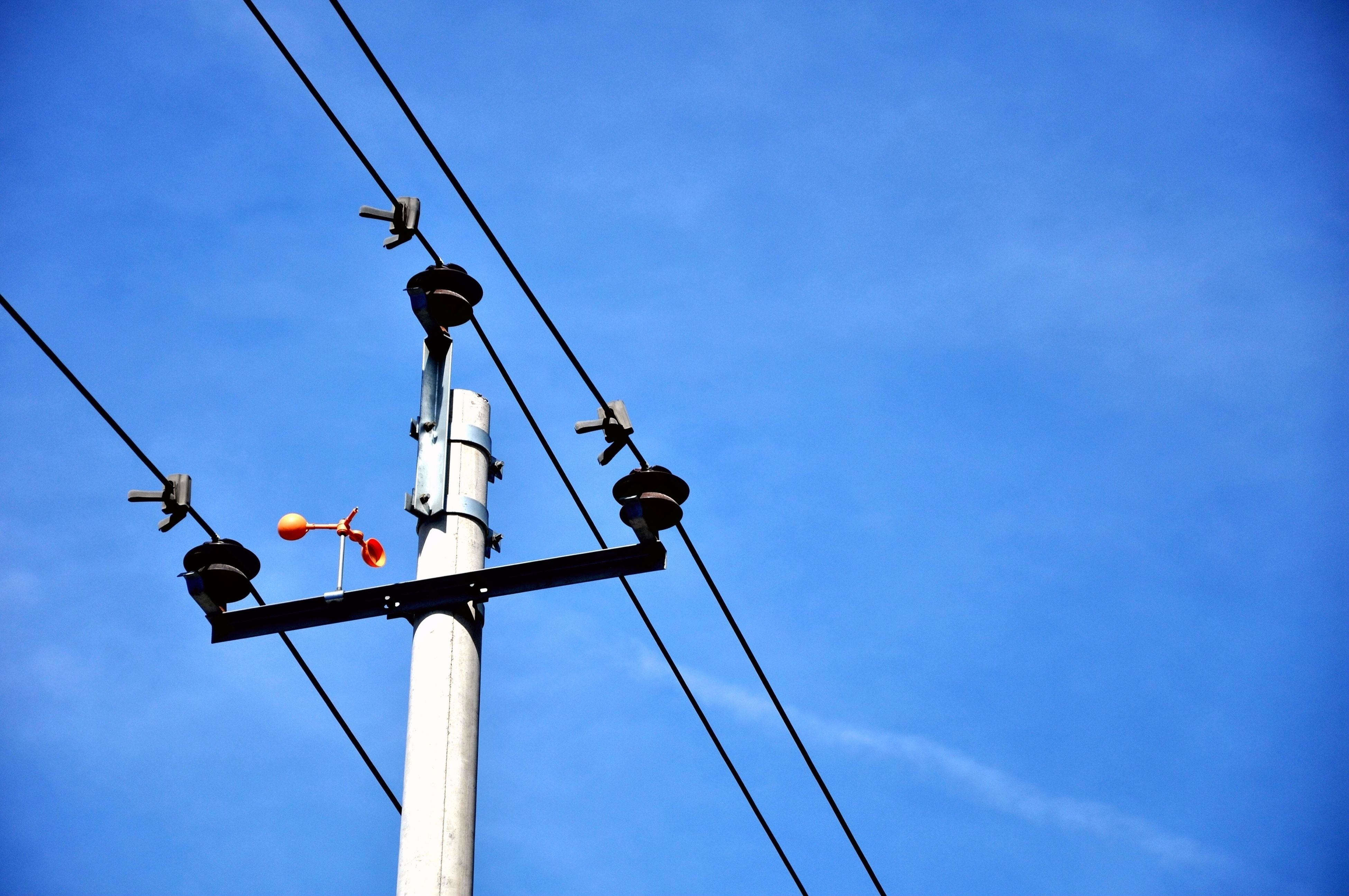 low angle view, blue, street light, electricity, lighting equipment, clear sky, power line, pole, cable, sky, technology, communication, power supply, guidance, electricity pylon, connection, road signal, fuel and power generation, day, outdoors