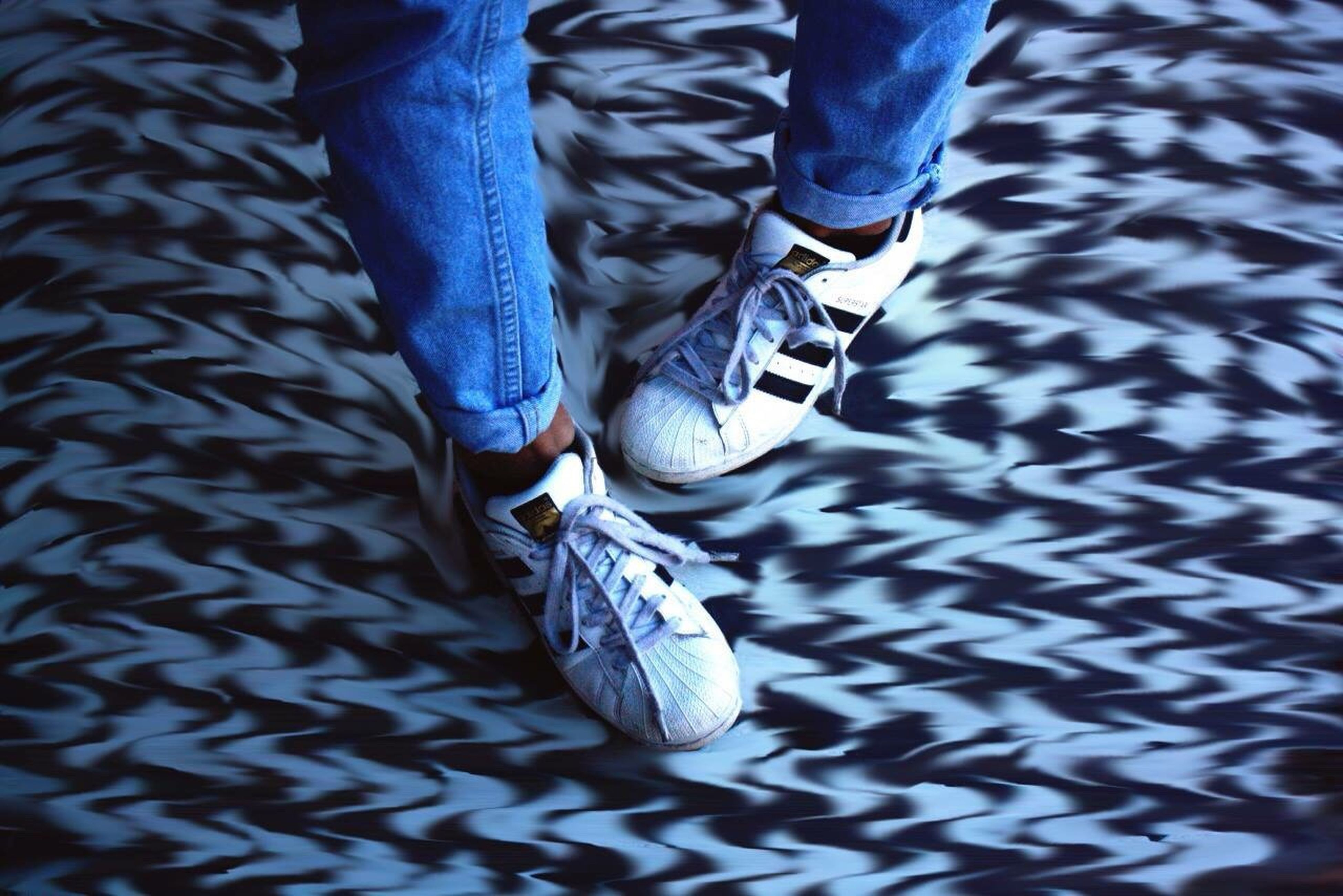 low section, shoe, person, footwear, jeans, blue, indoors, close-up, high angle view, part of, pattern, fashion, human foot, unrecognizable person, metal, pair, men