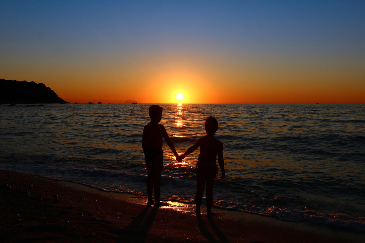 Rear View Of Silhouette Siblings Holding Hands At Beach Against Clear Sky During Sunset