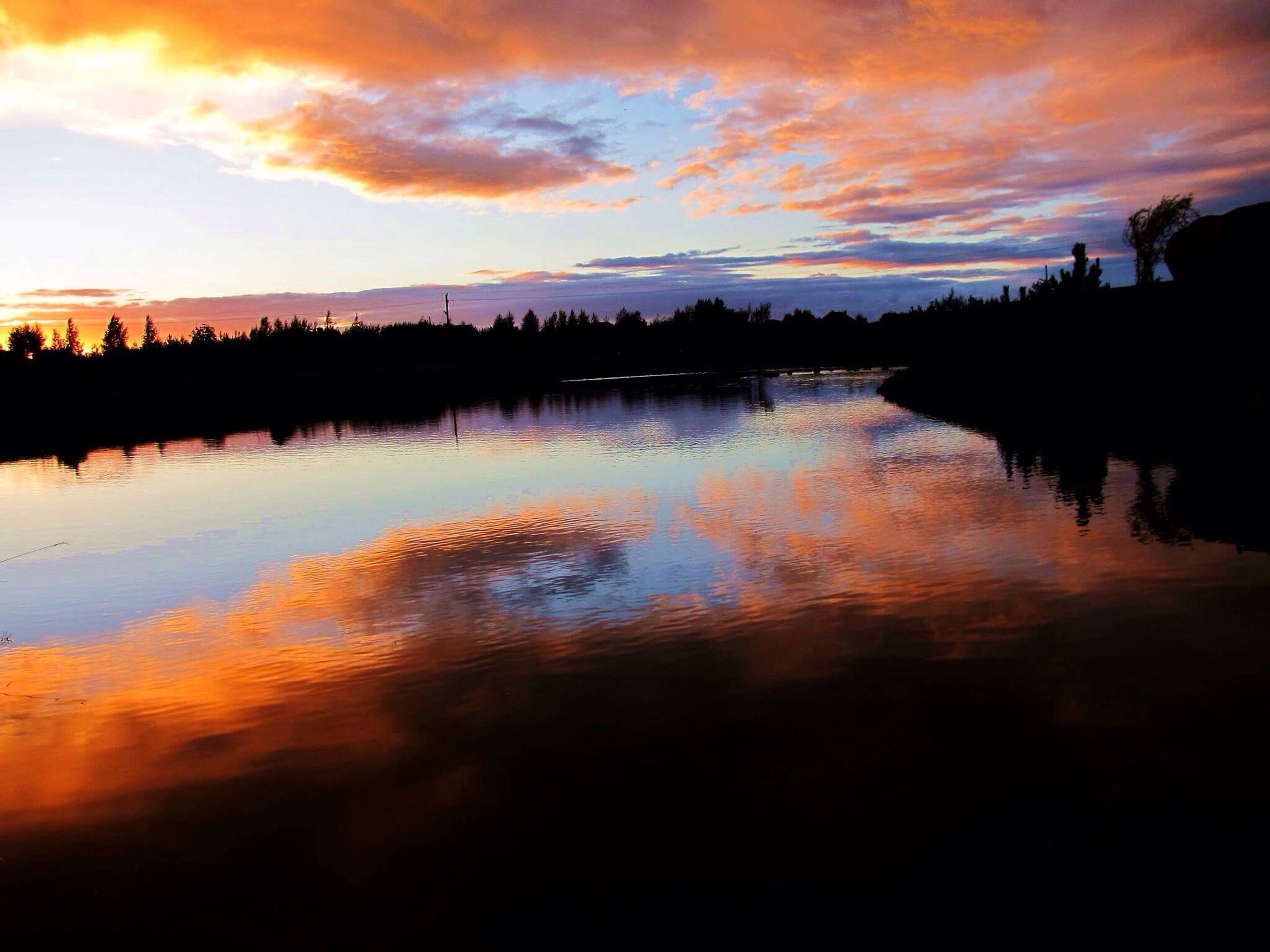 water, sunset, reflection, tranquil scene, scenics, silhouette, tranquility, lake, beauty in nature, idyllic, calm, sky, rippled, cloud, orange color, nature, cloud - sky, waterfront, atmospheric mood, atmosphere, majestic, dark, non-urban scene, moody sky, outdoors, dramatic sky, water surface, blue, outline, remote, vibrant color, countryside
