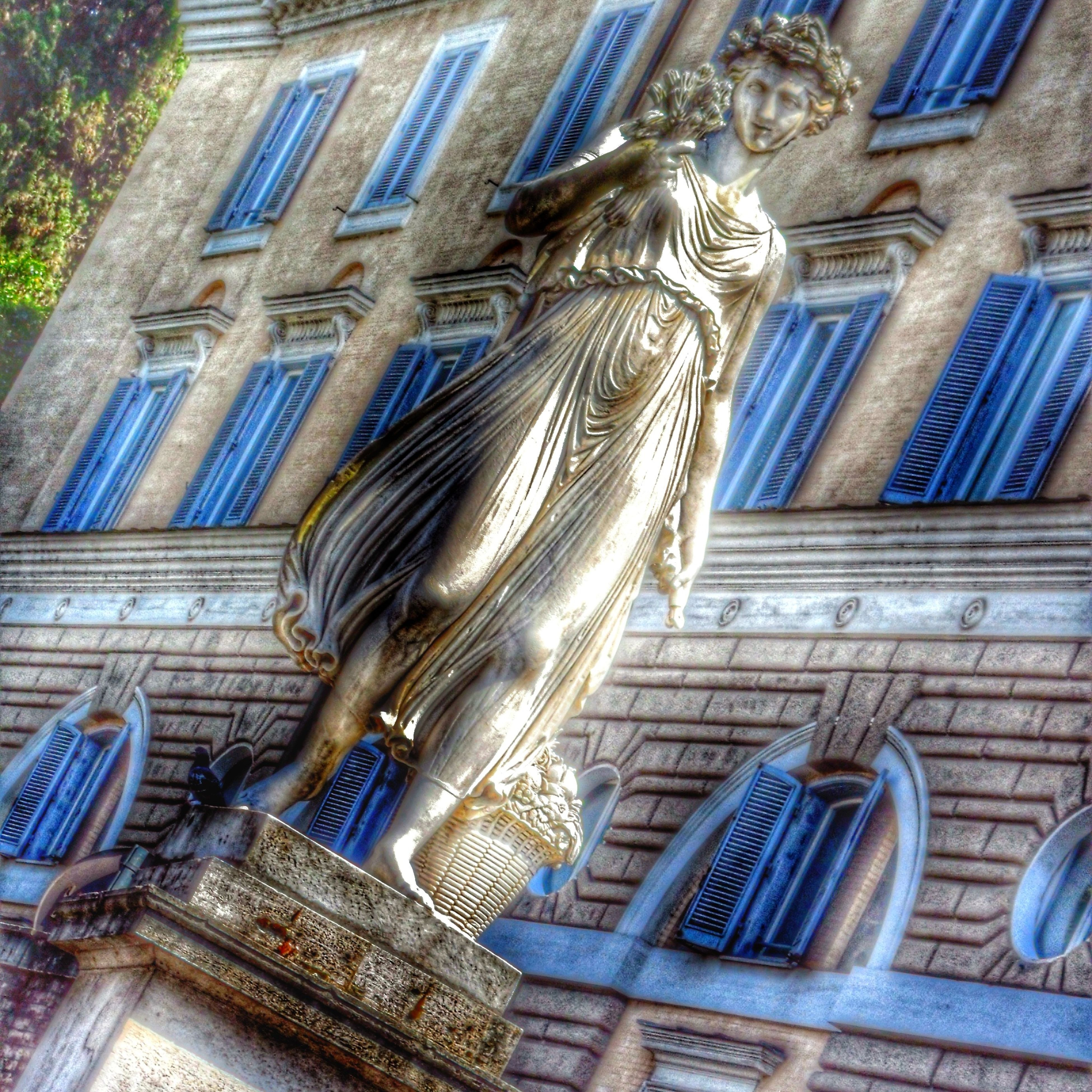 architecture, building exterior, built structure, low angle view, art and craft, building, art, statue, human representation, city, sculpture, window, creativity, day, blue, outdoors, no people, residential building, facade