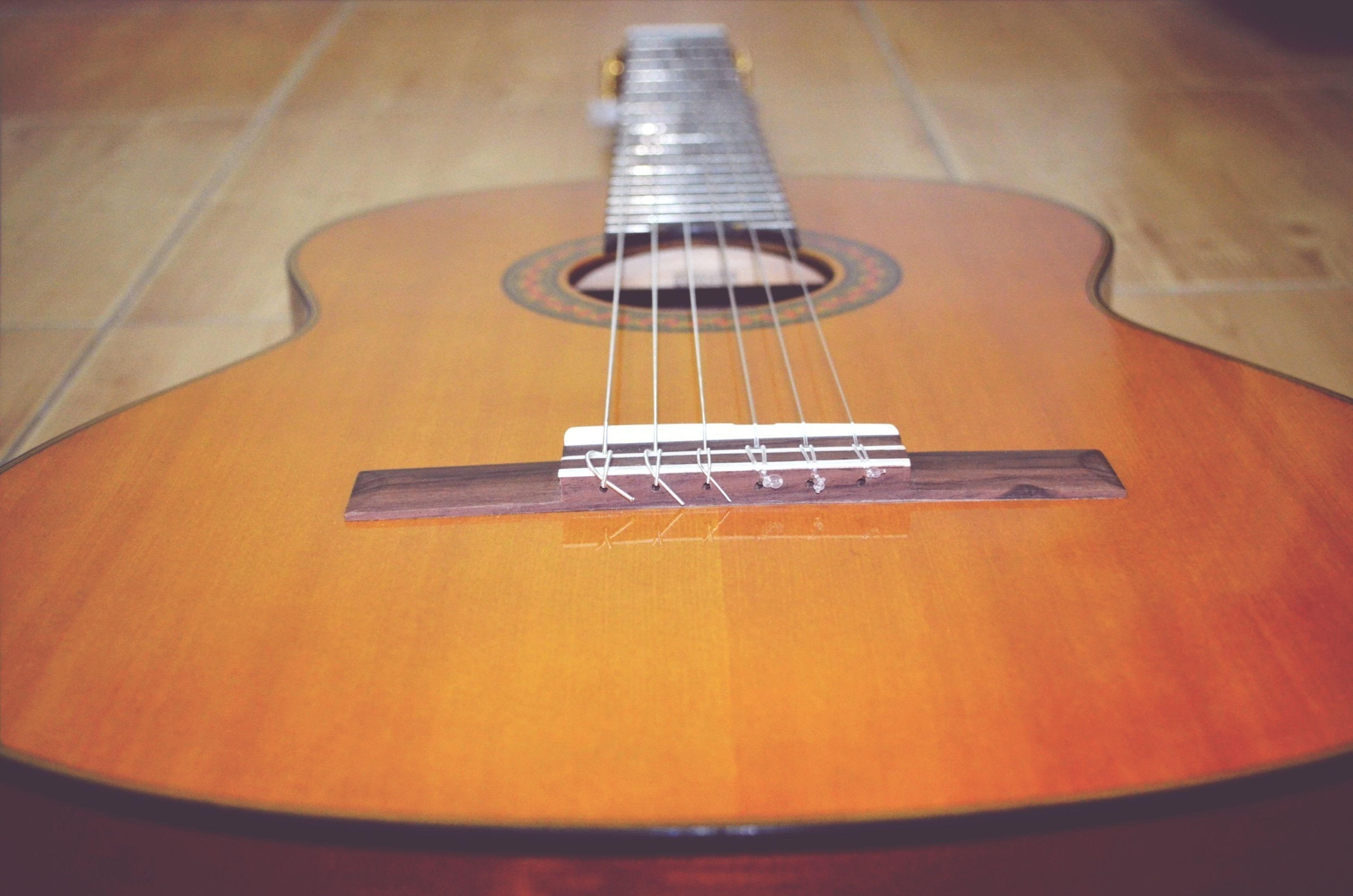 indoors, musical instrument, music, musical instrument string, musical equipment, guitar, arts culture and entertainment, string instrument, still life, acoustic guitar, close-up, illuminated, technology, high angle view, no people, table, selective focus, piano, wood - material, piano key