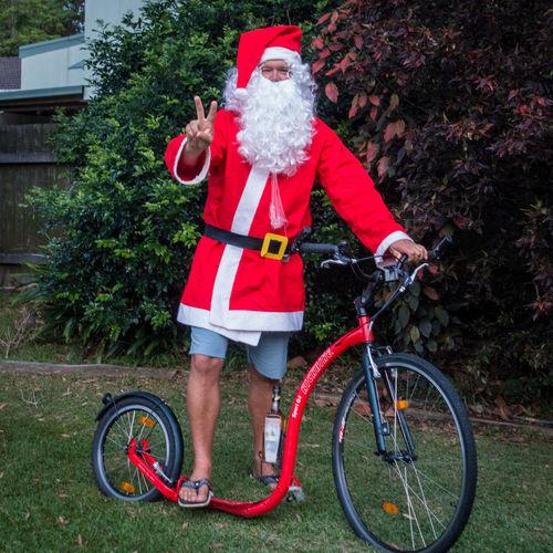 Santa in shorts and flip-flops on kickbike Bicycle Christmas Cycling Flip-flops Fun Kickbike Land Vehicle Red Riding Santa Shorts Summer