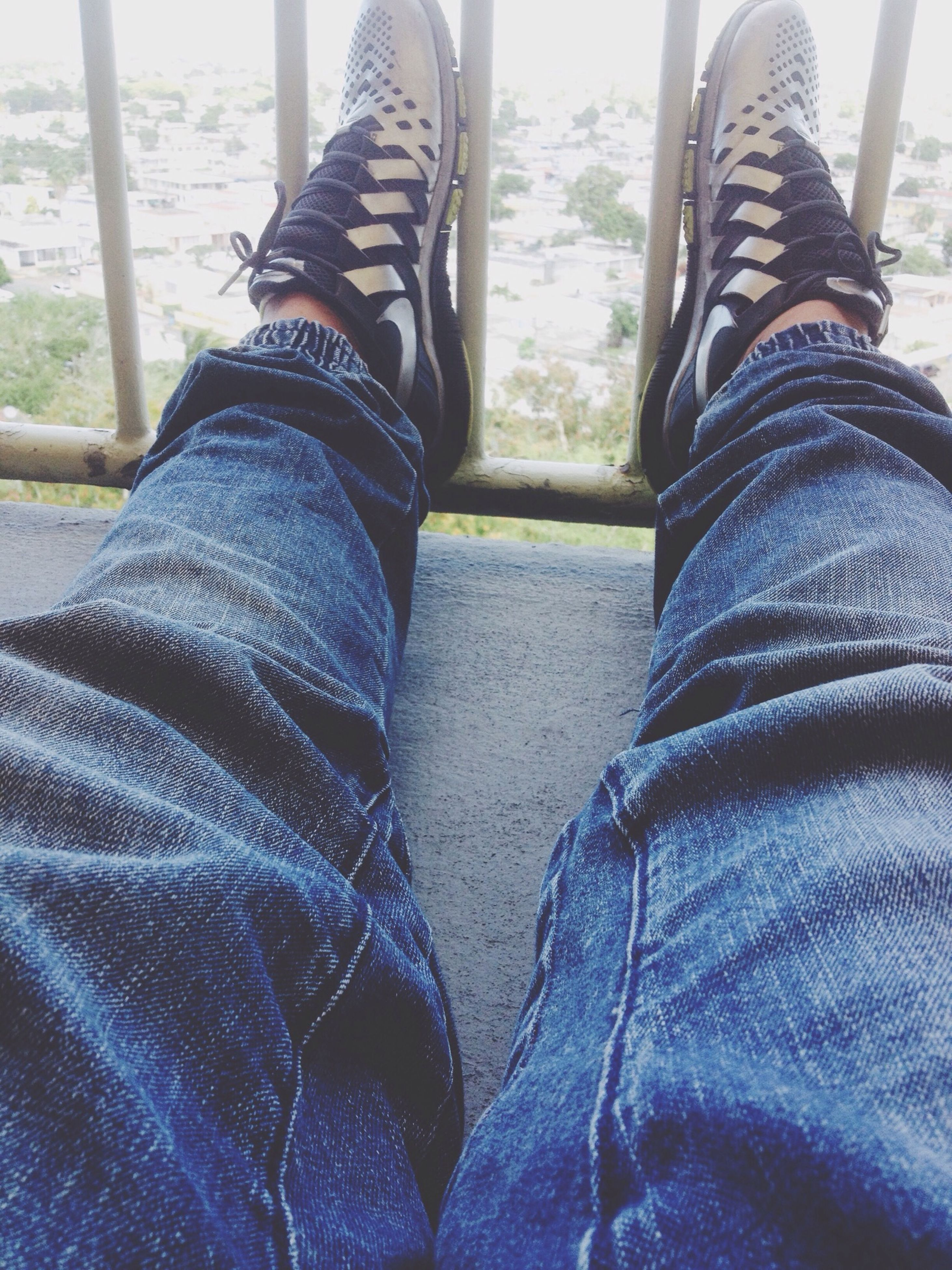 low section, person, shoe, jeans, lifestyles, human foot, personal perspective, standing, leisure activity, casual clothing, footwear, men, sitting, relaxation, high angle view, day, sunlight