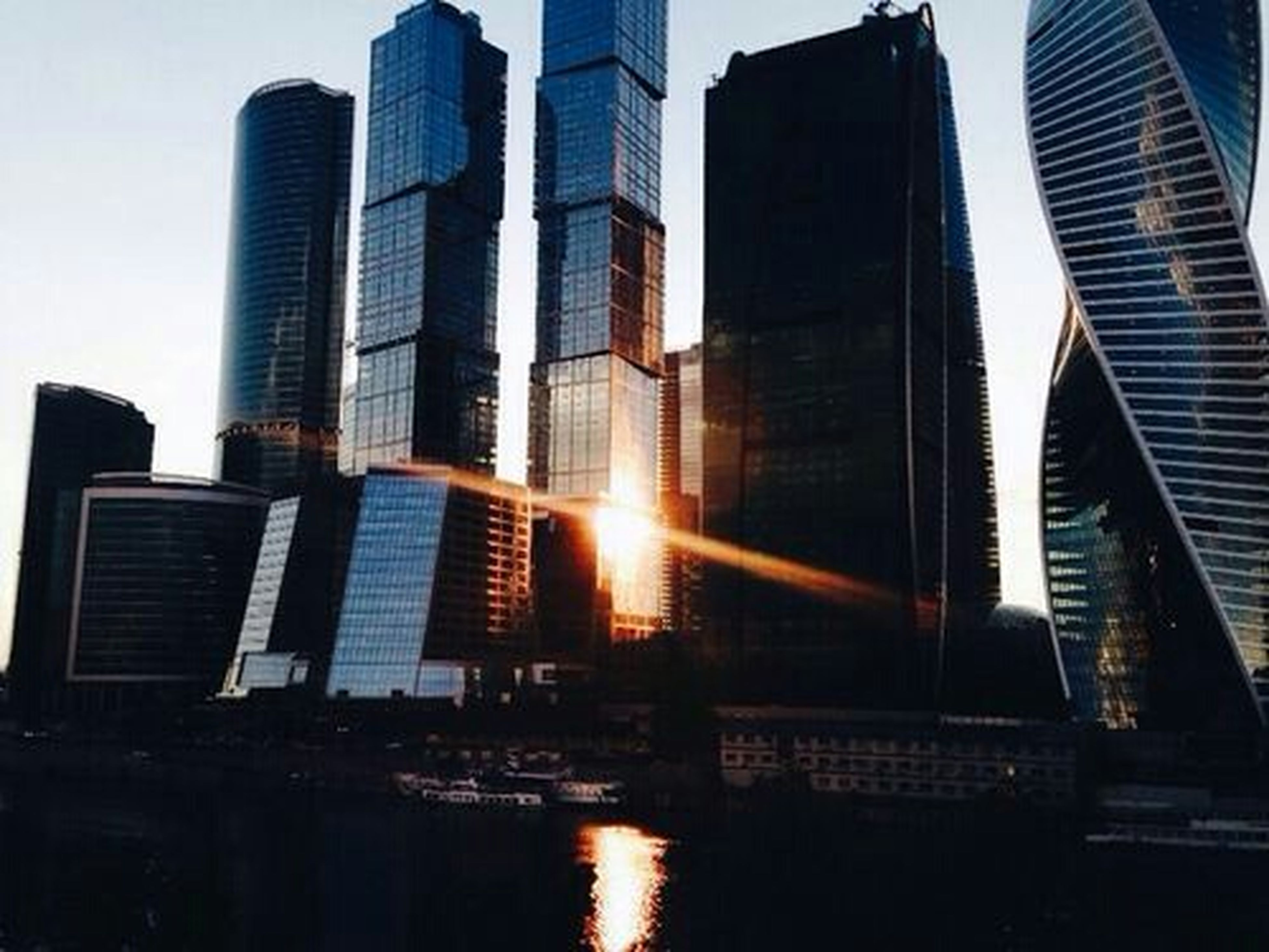 architecture, building exterior, built structure, city, reflection, skyscraper, modern, office building, building, water, sky, tall - high, sunlight, tower, waterfront, low angle view, sun, glass - material, sunset, river
