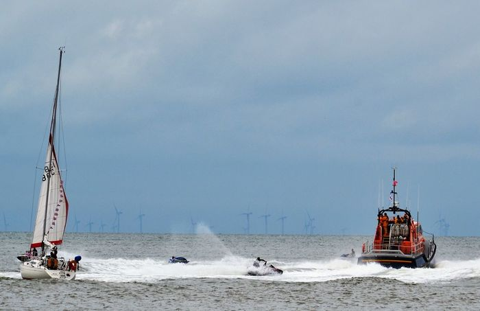 RNLI Lifeboat Day at Fleetwood, Lancashire UK on the River Wyre estuary, Knott End on Sea. RNLI Lifeboat in the right of the picture with a local sailing school yacht on the left. In between are jet skis creating waves and sea spray. Cloud - Sky Day Horizon Over Water Jet Skis Lancashire UK Lifeboat Lifeboat RNLI Nautical Vessel Sail Sailboat Sailboat Photography Scenics Sea Sea Spray Sky Transportation Water Wave Waves Wind Farm Seascape Yacht