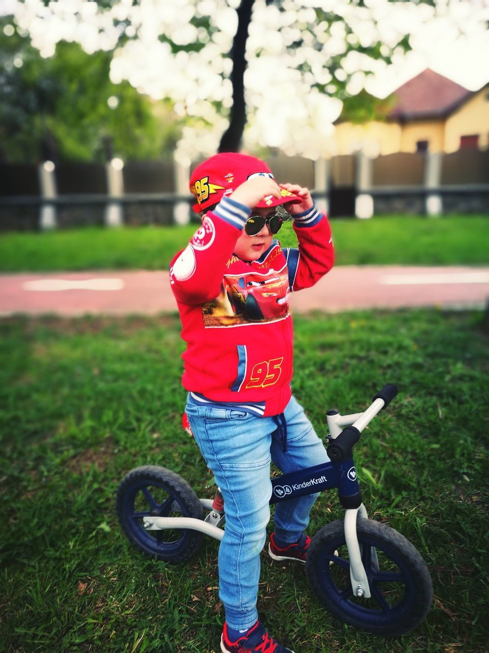 grass, headwear, helmet, full length, field, sports helmet, real people, day, one person, bicycle, leisure activity, transportation, outdoors, childhood, sports clothing, cycling helmet, lifestyles, nature, people