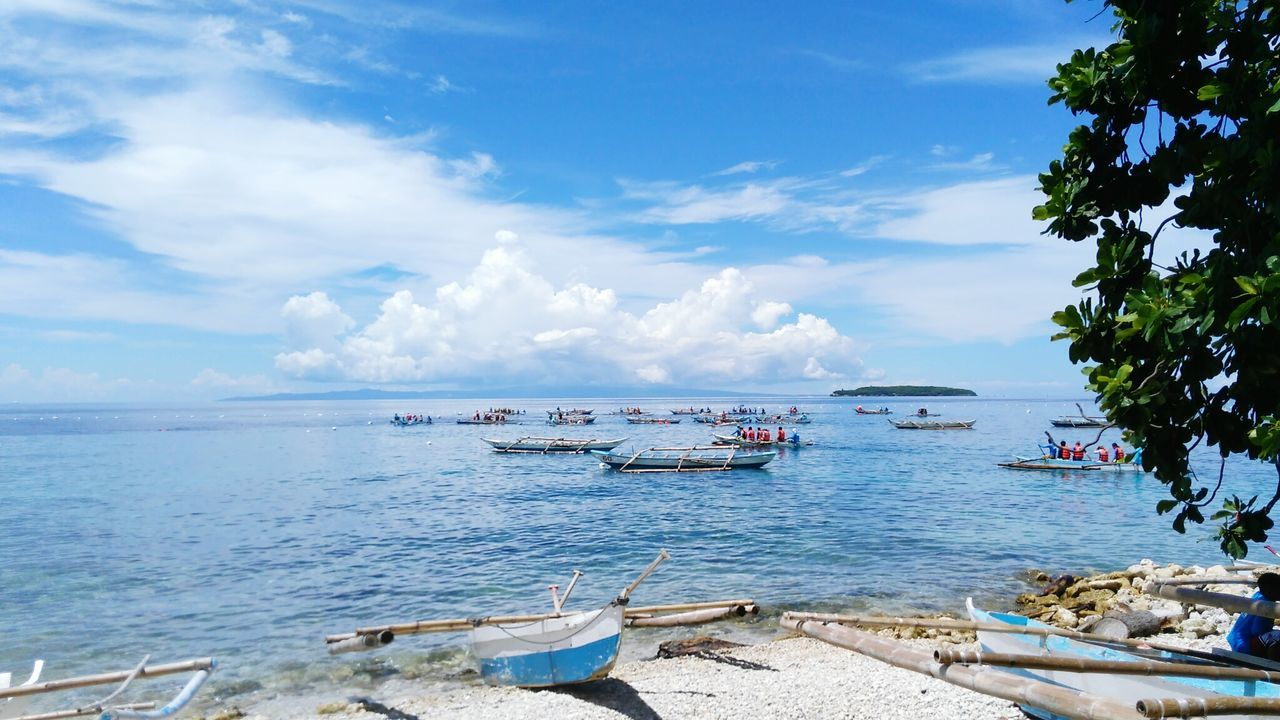 nautical vessel, transportation, sky, mode of transport, sea, boat, cloud - sky, water, nature, beauty in nature, scenics, day, outdoors, moored, beach, tranquility, tranquil scene, no people, outrigger, horizon over water, tree, jet boat