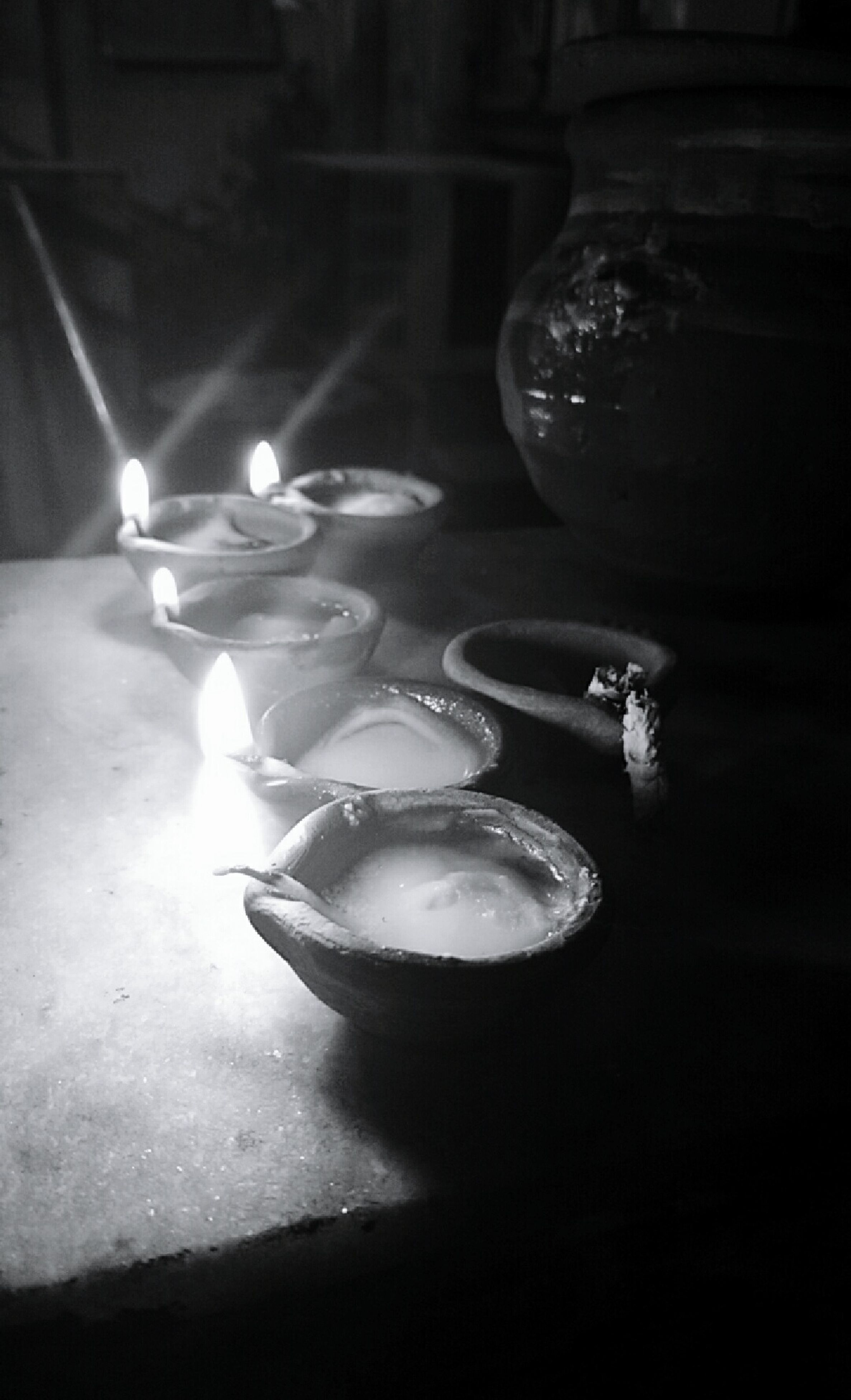 indoors, night, illuminated, burning, light - natural phenomenon, reflection, flame, dark, close-up, high angle view, candle, glass - material, glowing, unrecognizable person, men, shadow, table, lighting equipment