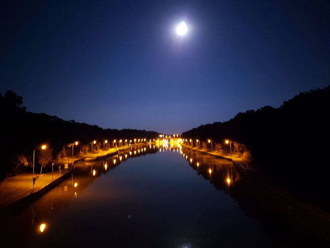 Illuminated Night Reflection Water Street Light Illuminated Night Reflection Water Street Light Dark Calm Moon Clear Sky Waterfront Sky Tranquil Scene Diminishing Perspective Outdoors Standing Water Long Scenics Canal Tranquility Architecture
