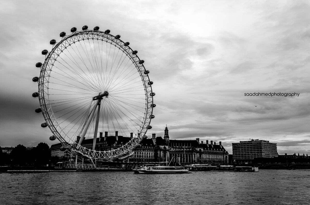 Millennium Wheel By River Against Cloudy Sky