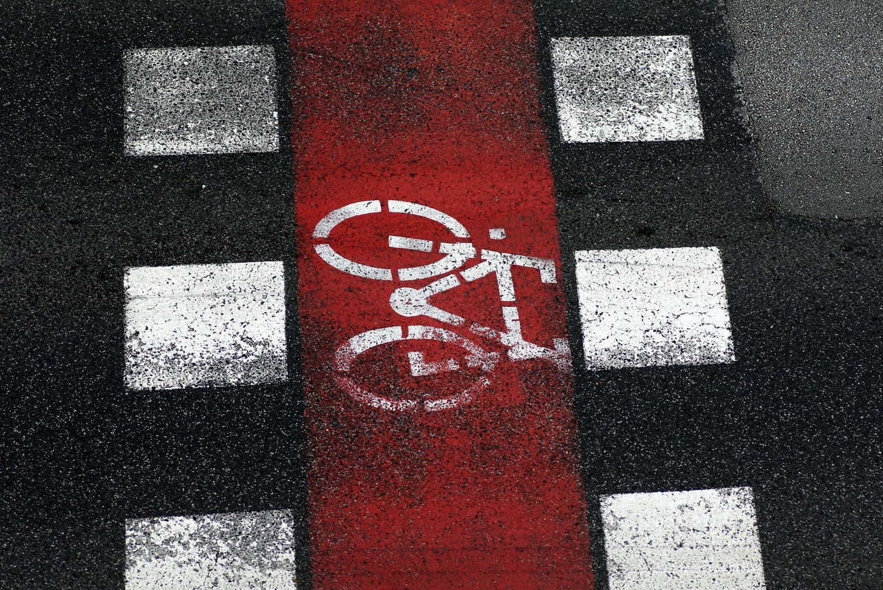 High angle view of zebra crossing bicycle sign on road. Asphalt Bicycle Icon Bicycle Representation City City Life Close-up Cycling Day Guidance High Angle View No People Outdoors Red Road Marking Road Sign Road Signage Signage Street Transport Transportation Zebra Crossing