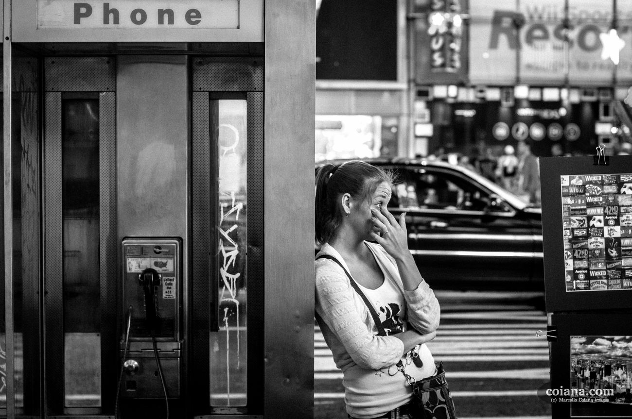 a girl next to phone booth removing something out from her eyes in nyc. Adult Adults Only Blackandwhite City Communication Day Girl Lifestyles One Person One Woman Only One Young Woman Only Only Women Outdoors People Phone Real People Streetphotography Technology Women Young Adult