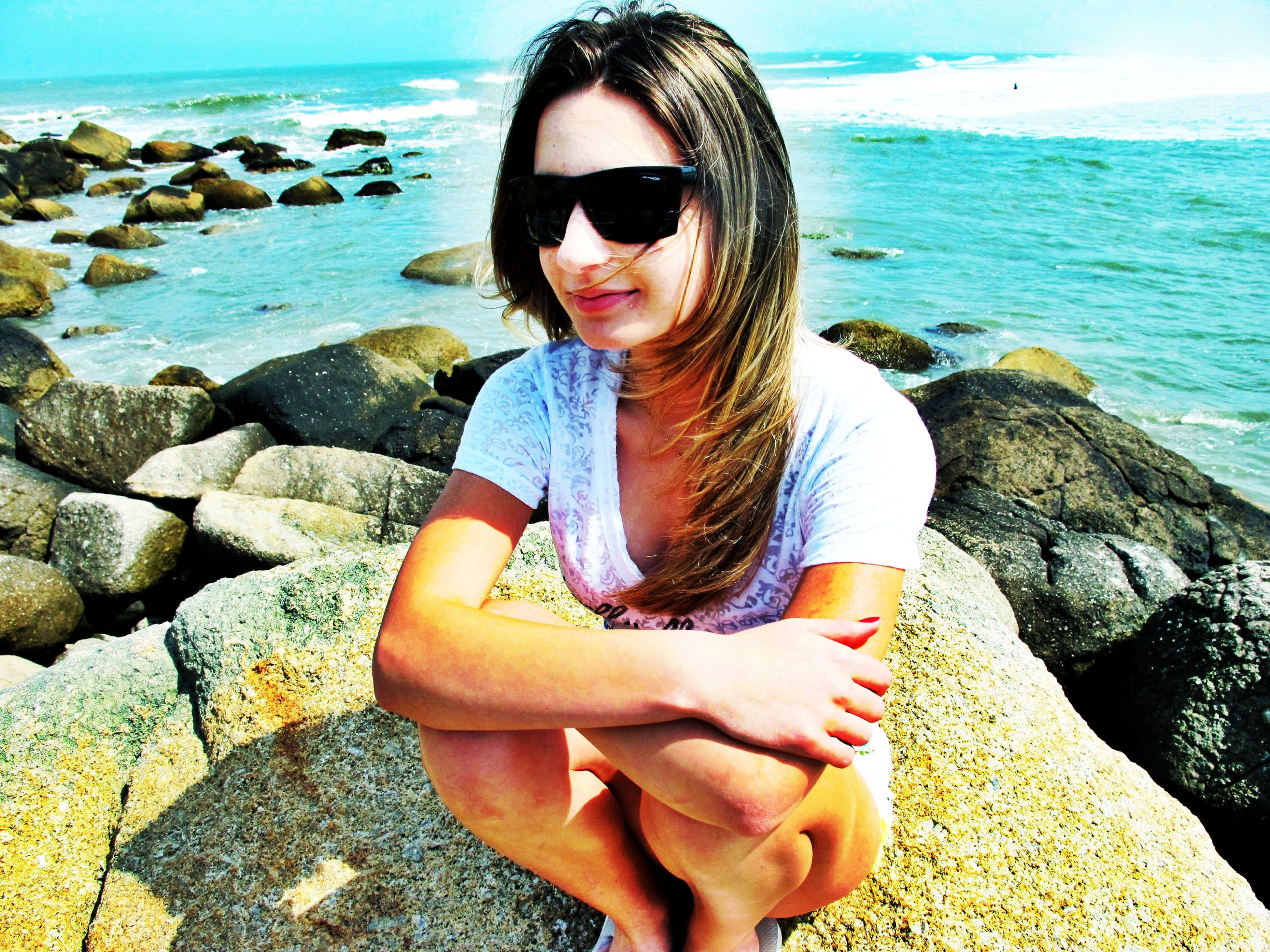 lifestyles, sea, water, beach, leisure activity, young adult, person, sunglasses, vacations, shore, young women, portrait, rock - object, looking at camera, casual clothing, sitting, sunlight, front view