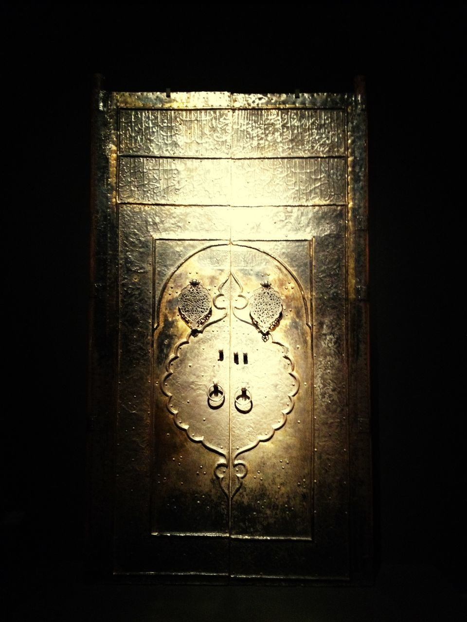 Closed Gold Door With Arabic Text Against Black Background