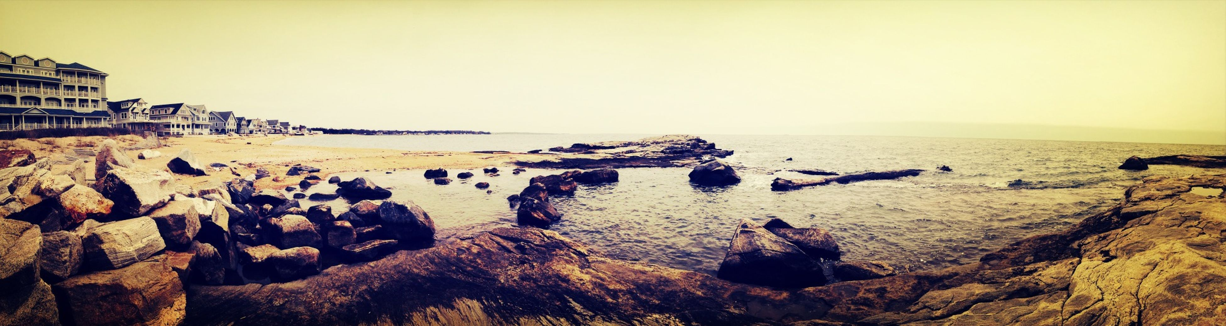 sea, water, clear sky, horizon over water, beach, rock - object, copy space, tranquil scene, scenics, shore, tranquility, beauty in nature, nature, rock formation, rock, coastline, sky, idyllic, outdoors, incidental people
