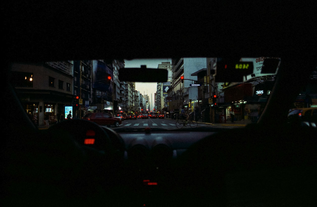 car, transportation, night, land vehicle, mode of transport, vehicle interior, illuminated, car interior, architecture, dark, built structure, city, building exterior, no people, outdoors