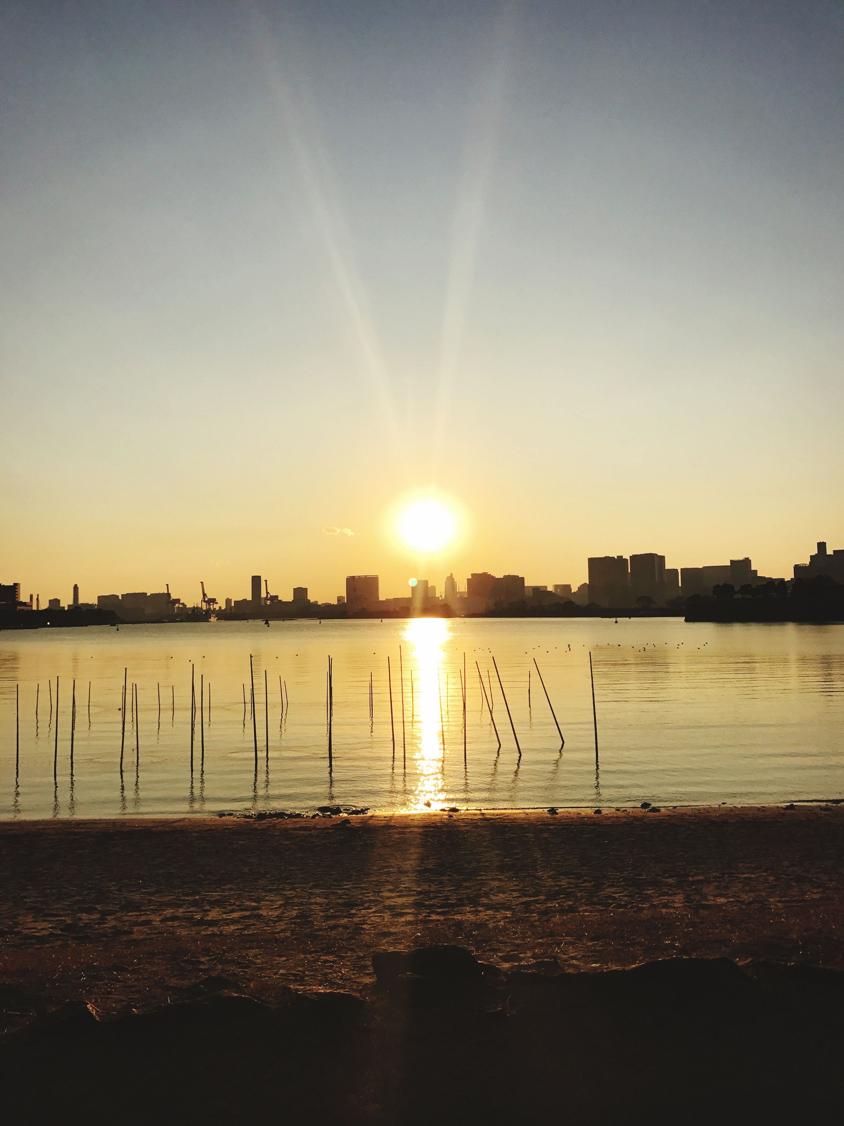 sun, sunset, water, sunbeam, sunlight, beauty in nature, lens flare, nature, sky, built structure, scenics, orange color, building exterior, reflection, tranquility, no people, sea, outdoors, tranquil scene, silhouette, architecture, city, vapor trail, day