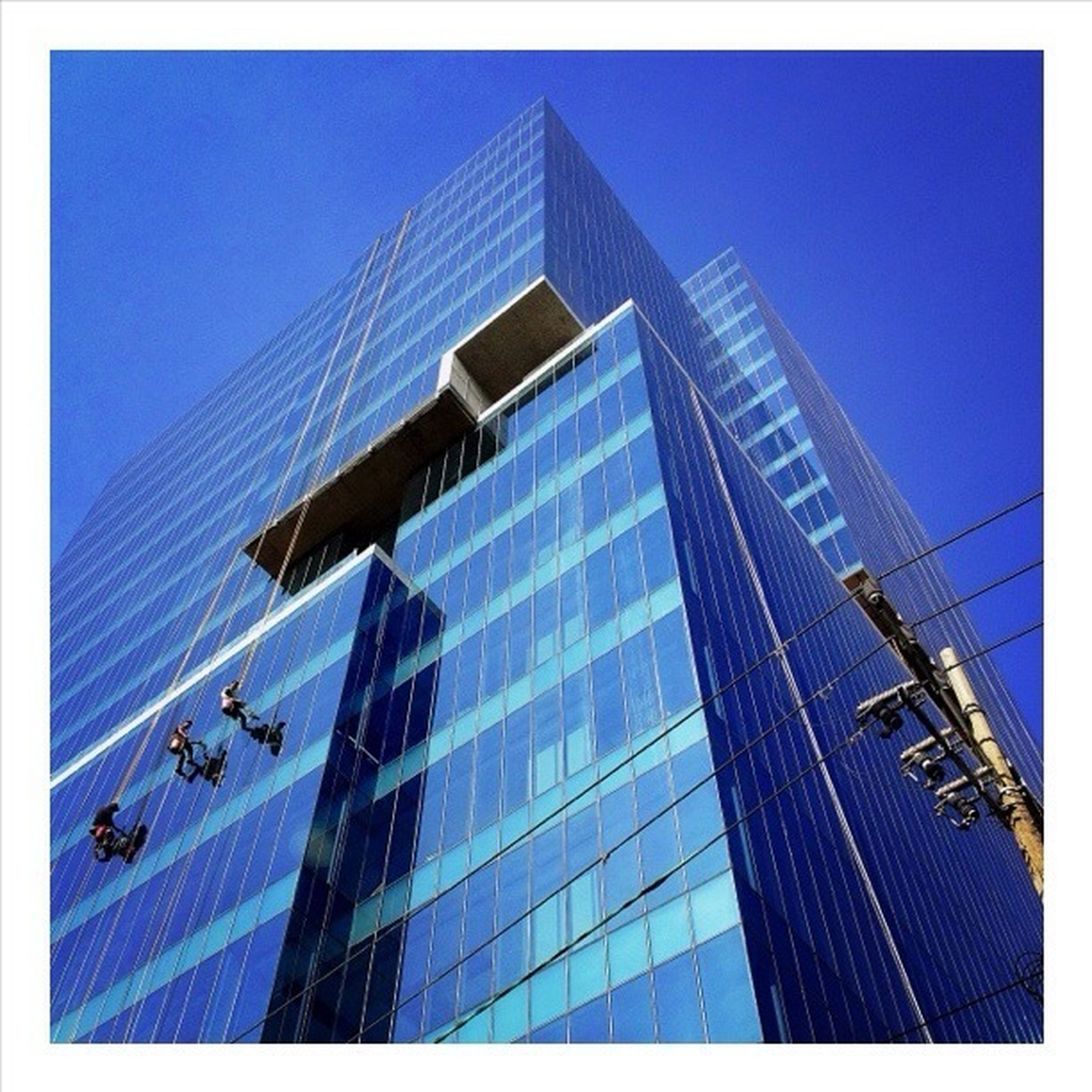 transfer print, architecture, building exterior, built structure, blue, auto post production filter, clear sky, low angle view, city, modern, city life, day, building, sky, sunlight, office building, outdoors, transportation, large group of people