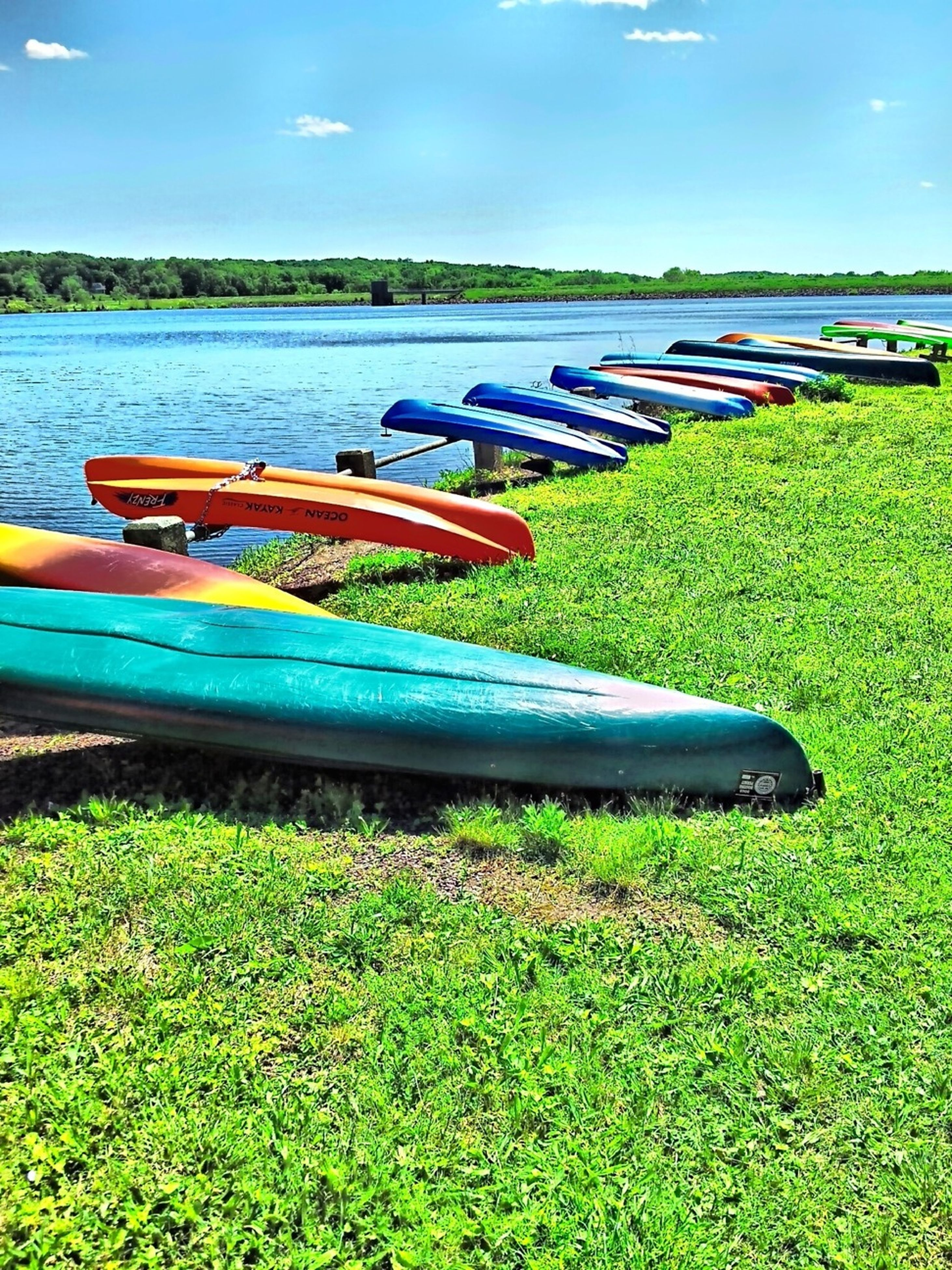 transportation, grass, mode of transport, moored, nautical vessel, blue, water, boat, field, green color, no people, tranquility, lake, day, outdoors, nature, in a row, sky, absence, tranquil scene