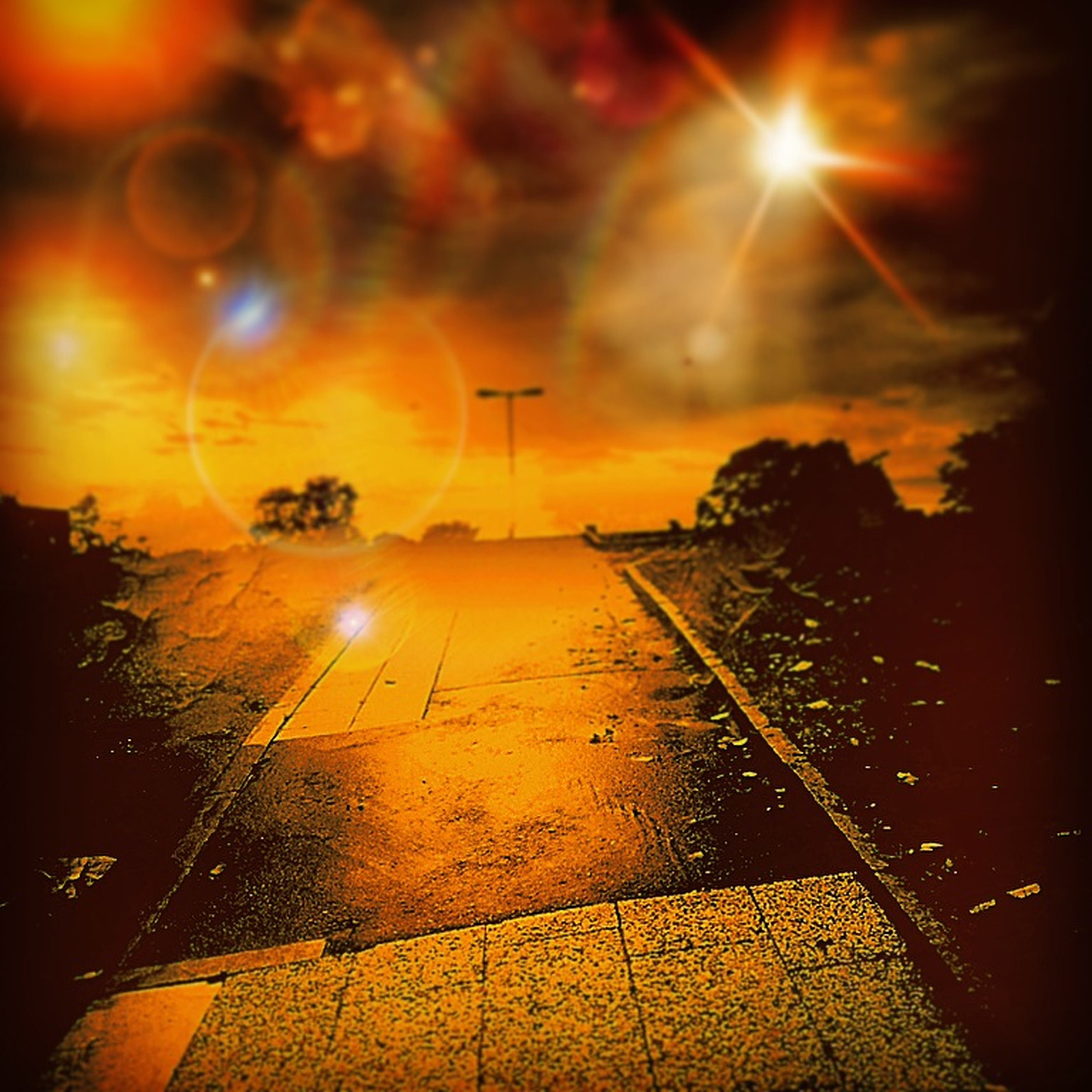 sunset, sun, transportation, lens flare, street light, orange color, illuminated, sky, sunbeam, sunlight, road, street, lighting equipment, the way forward, outdoors, no people, car, mode of transport, glowing, nature