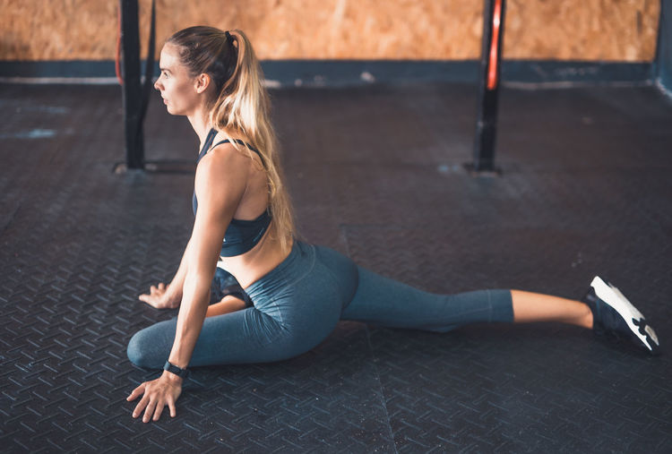 Exercising Indoor Activities Musculation  Squat Stretching Legs Blonde Exercising Cross Training Crossfit Crossfit Girl Energy Flexibility Healthy Lifestyle Kettlebell  Leisure Activity Lifestyles Muscular Build One Person Real People Sport Clothing Stretching Training Weightlifting Wellbeing Workout Yoga