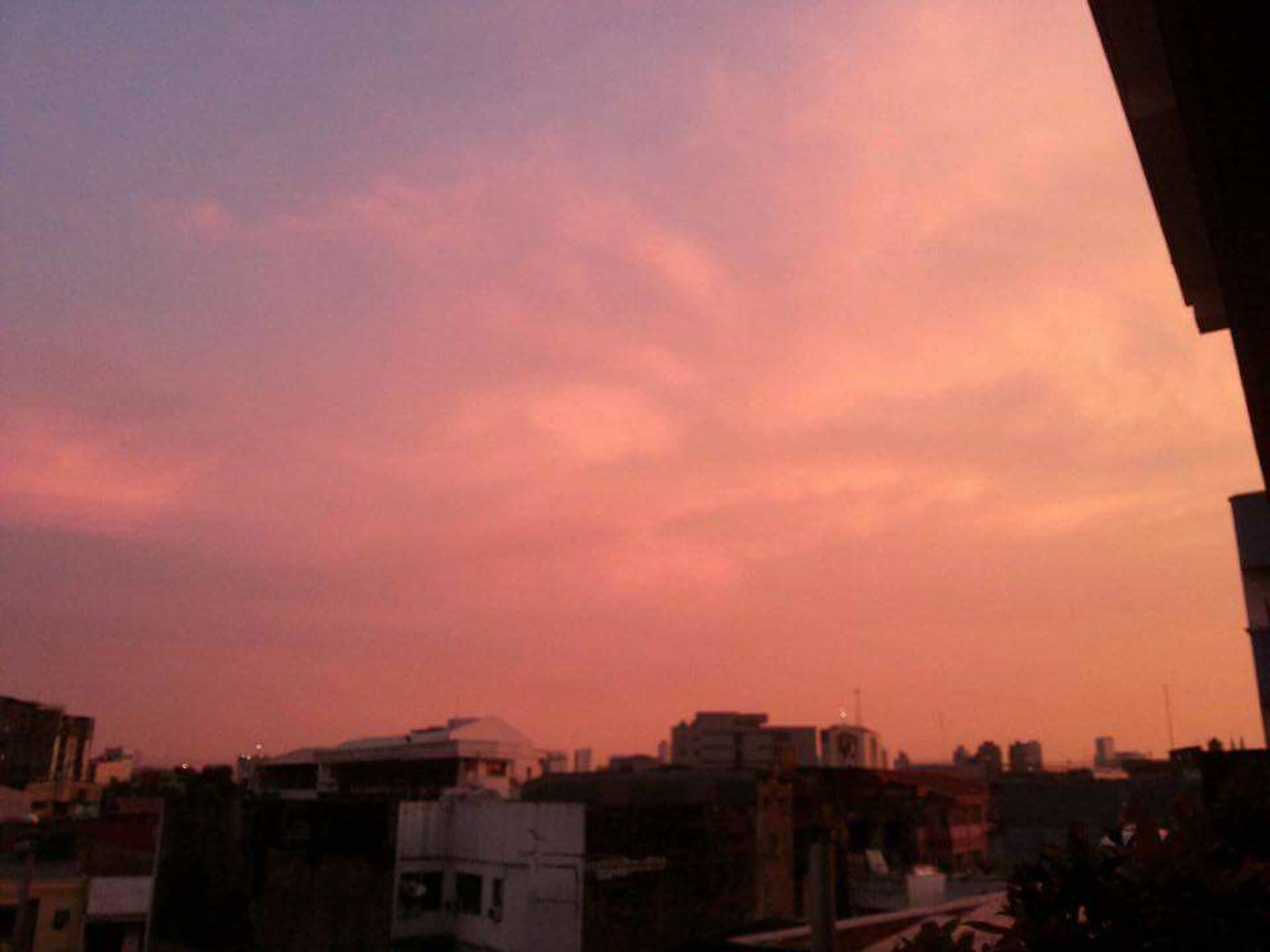architecture, building exterior, built structure, city, residential building, sunset, residential structure, sky, cityscape, city life, cloud - sky, residential district, cloud, romantic sky, apartment, building story, town, outdoors, orange color, no people, high section, development, tall - high, wide shot, storm cloud, dramatic sky