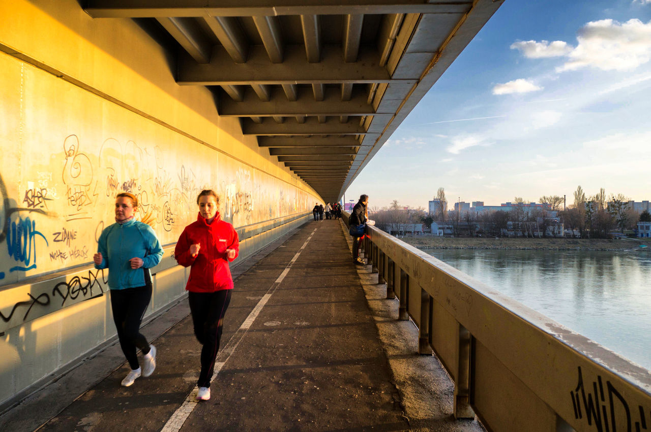 bridge - man made structure, built structure, river, architecture, water, connection, city, jogging, full length, city life, running, real people, lifestyles, bridge, outdoors, sports clothing, exercising, footbridge, women, building exterior, day, sky, cityscape