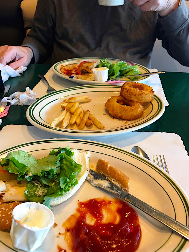 After burger lunch at diner Close-up Dining Out Eaten Fingers Finishing Up Fries Hands Indoors  Ketchup Leftovers Lettuce Lunch Meal One Person Onion Rings Phone Camera Place Mats Platters Savory Food Silverware  Table Unrecognizable Person