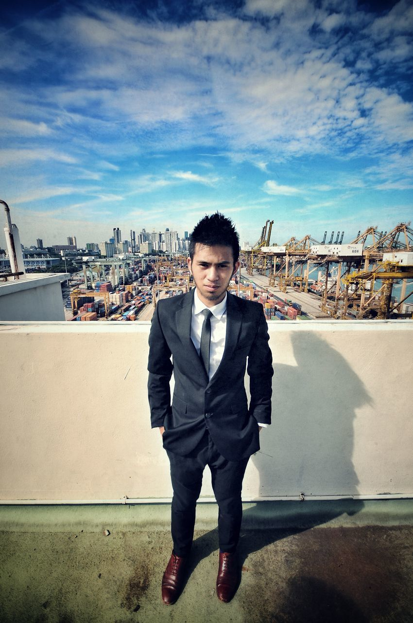 Full Length Portrait Of Young Businessman Standing Against Commercial Dock