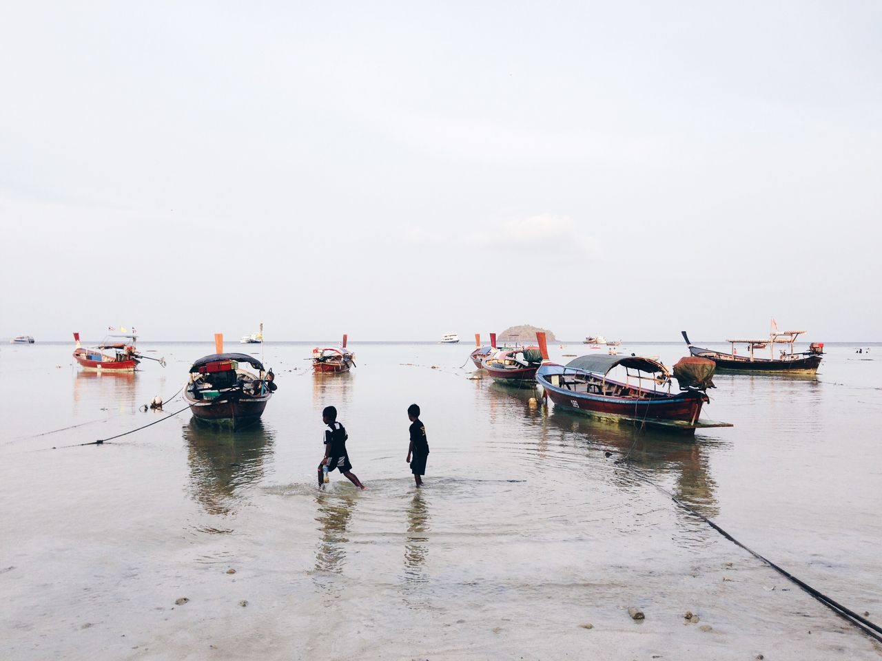 Boys Walking By Boats Moored At Sea Against Sky