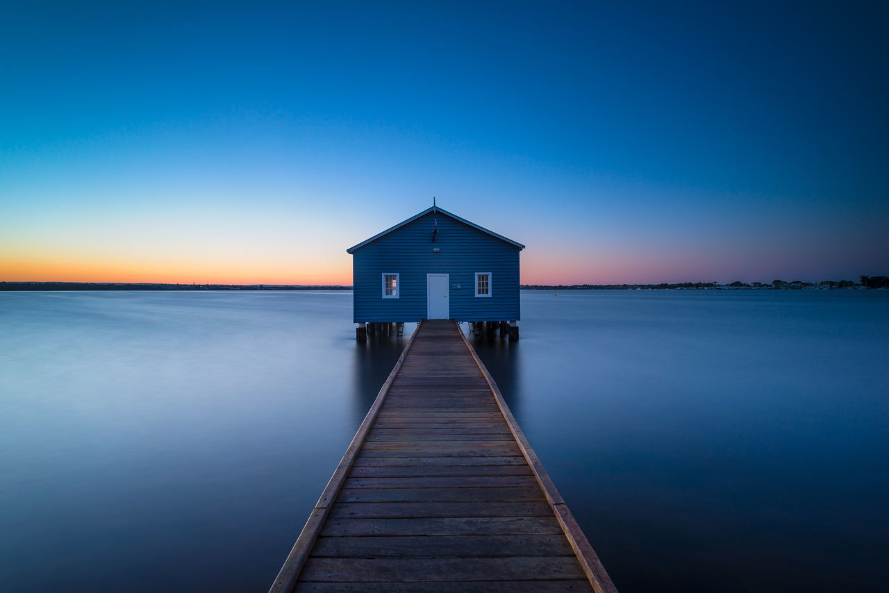 built structure, water, pier, sea, tranquil scene, tranquility, idyllic, blue, jetty, sky, outdoors, scenics, no people, horizon over water, architecture, beauty in nature, wood - material, clear sky, stilt house, nature, day, building exterior