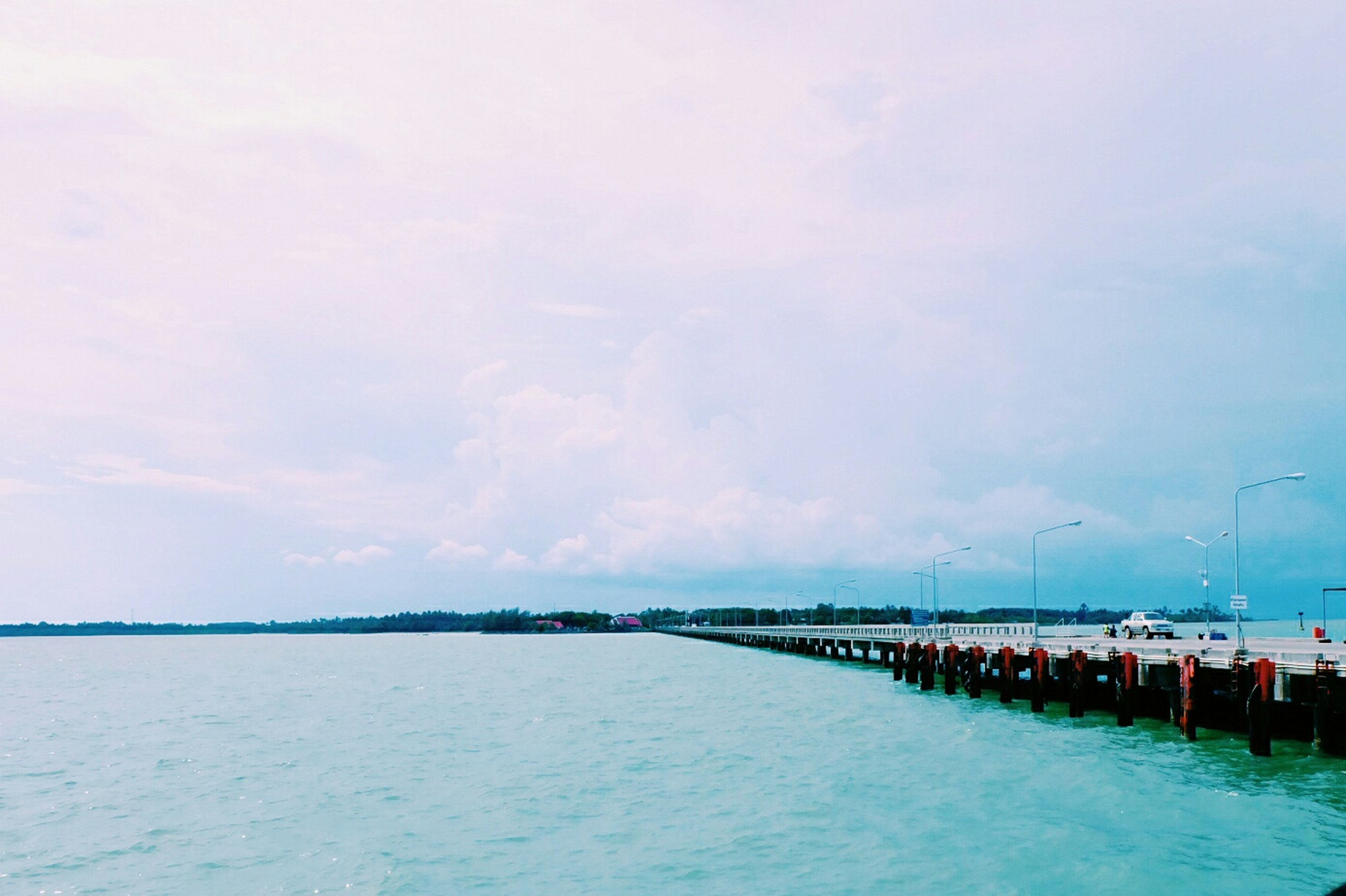 water, sea, sky, tranquil scene, tranquility, waterfront, scenics, beach, cloud - sky, beauty in nature, nature, built structure, horizon over water, pier, cloud, idyllic, cloudy, outdoors, day, blue
