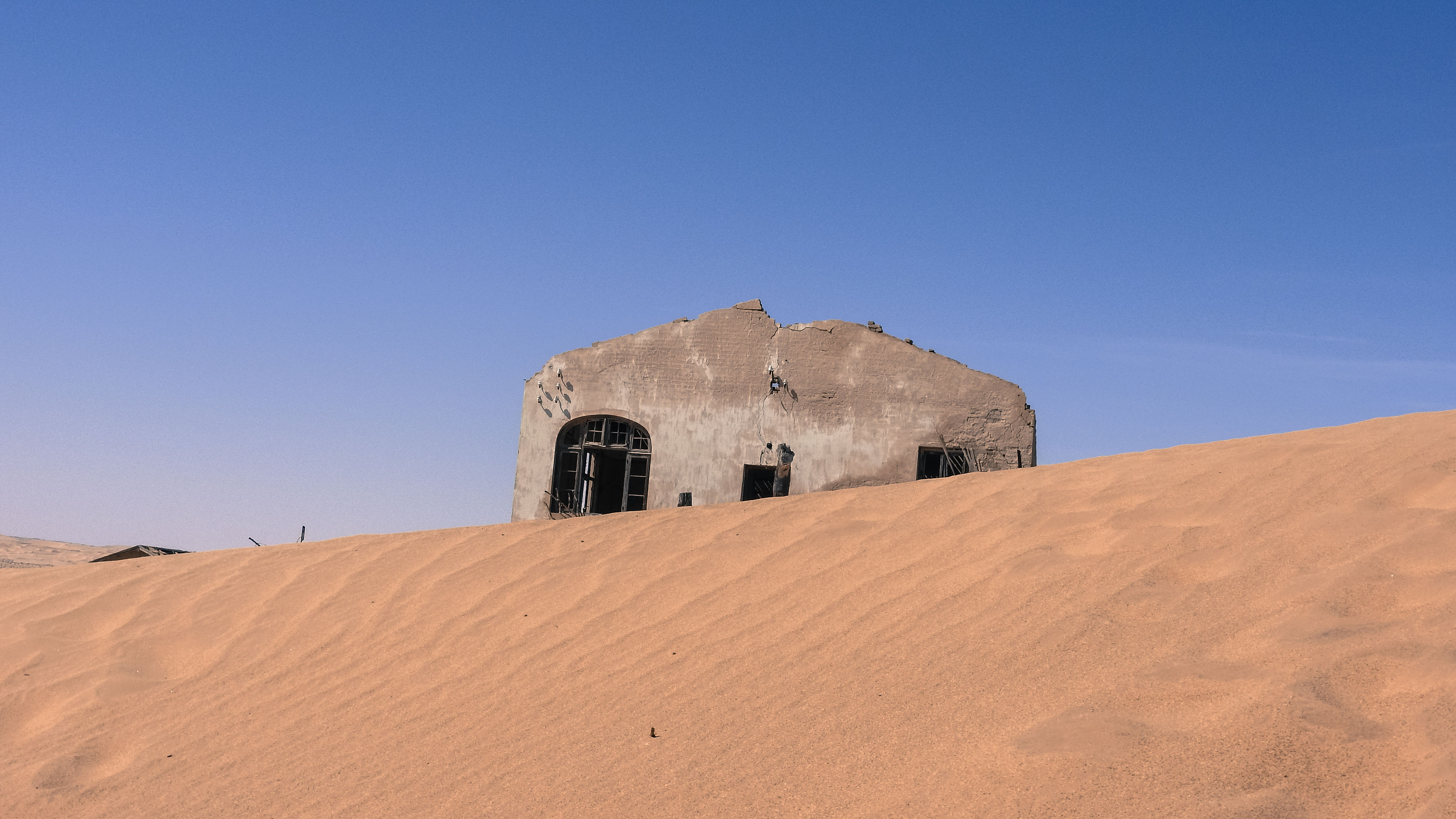 architecture, built structure, building exterior, blue, low angle view, clear sky, copy space, landscape, sand, hill, outdoors, tranquility, tranquil scene, summer, solitude, day, sky, rural scene, remote, no people, surface level, chapel, fort, non-urban scene, history, rock formation