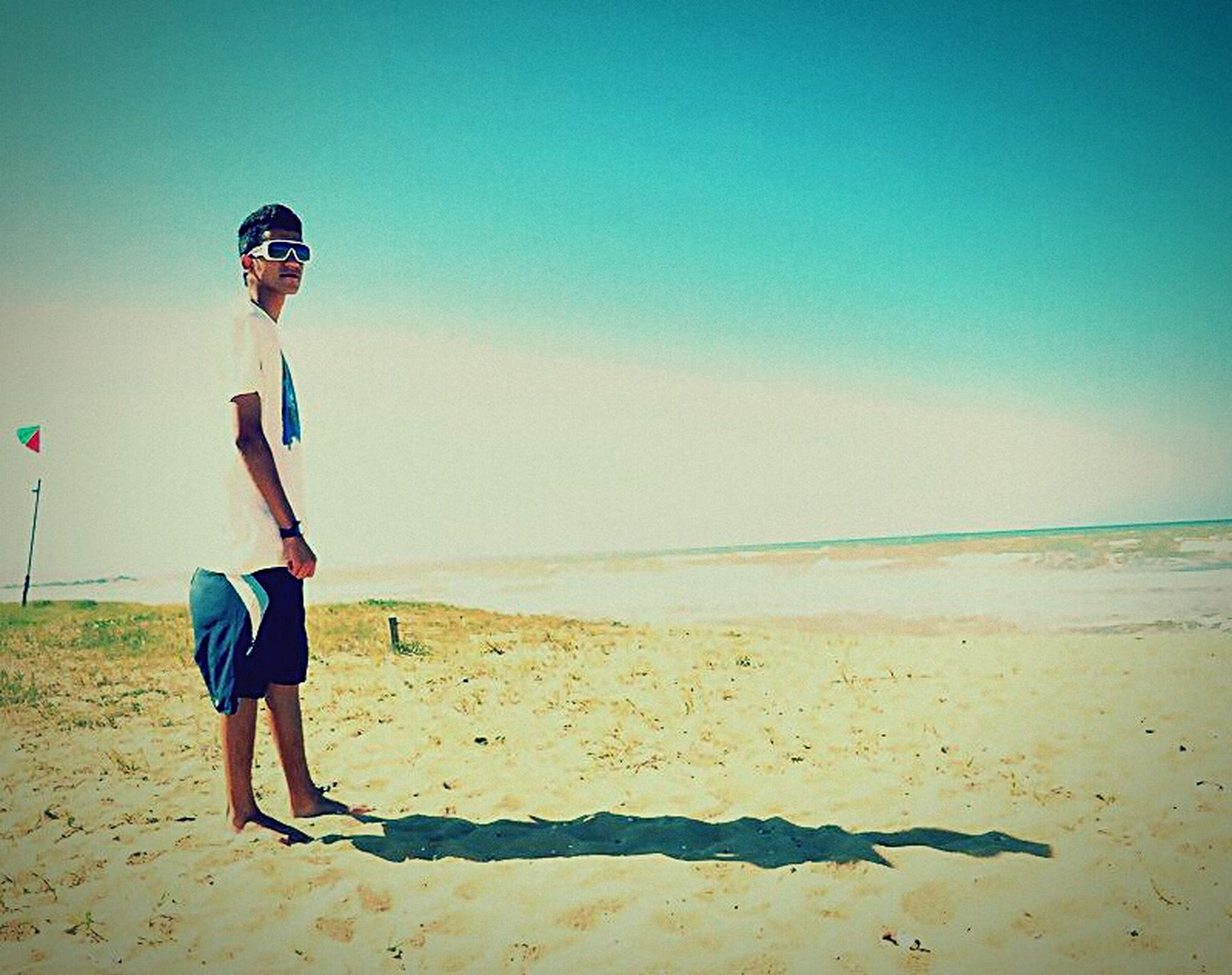 beach, sea, sand, full length, shore, horizon over water, lifestyles, leisure activity, standing, casual clothing, water, copy space, young adult, clear sky, vacations, person, beauty in nature, tranquil scene