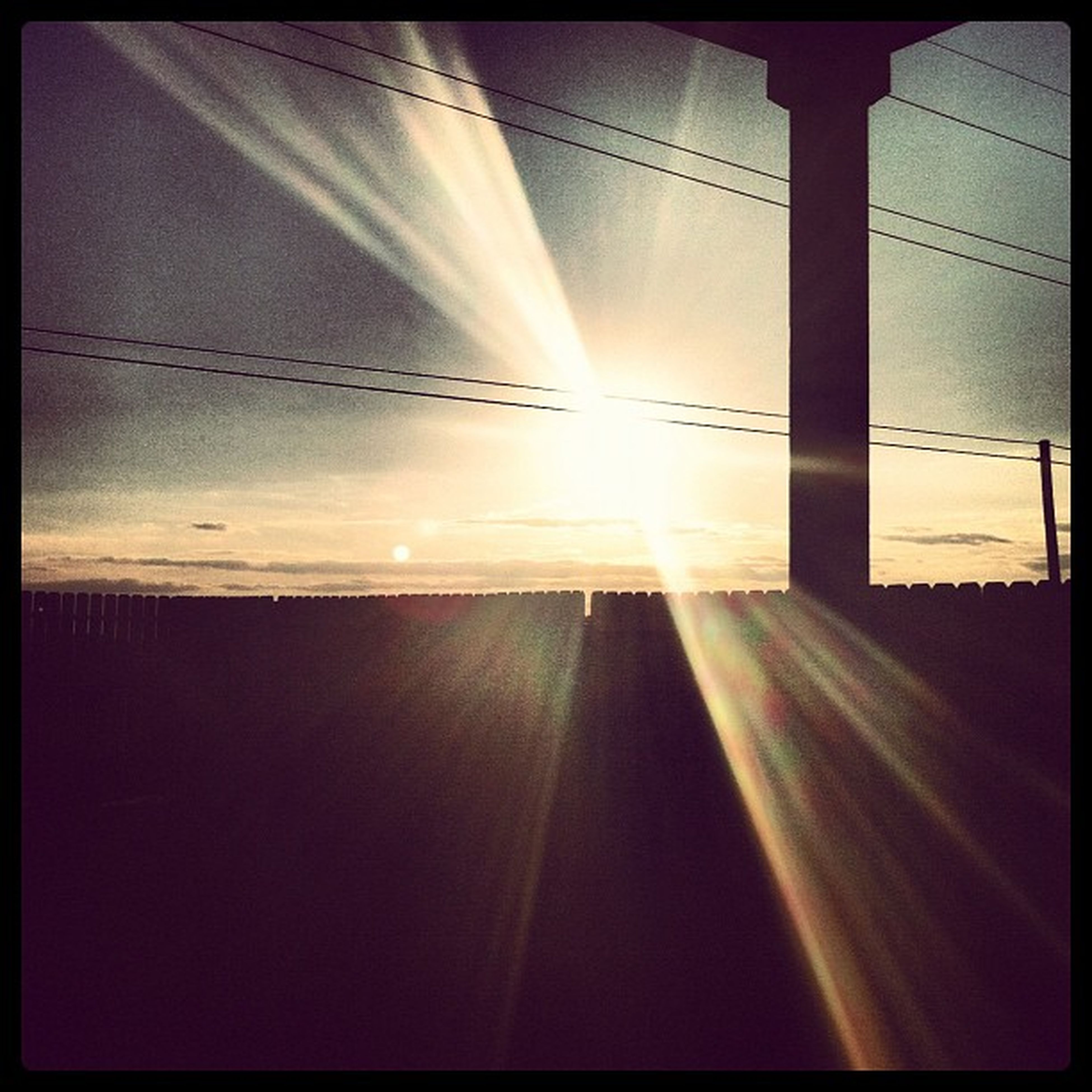 sun, sky, sunbeam, sunlight, lens flare, transfer print, sunset, cloud - sky, auto post production filter, cloud, tranquility, scenics, nature, power line, beauty in nature, built structure, no people, tranquil scene, outdoors, silhouette