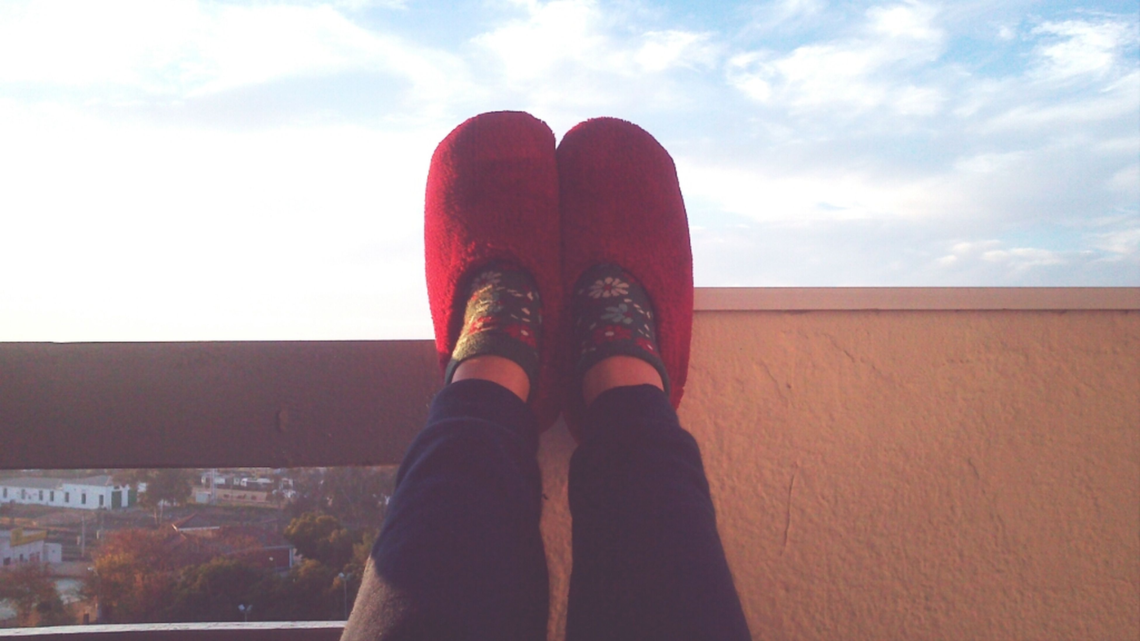 low section, person, shoe, personal perspective, sky, standing, lifestyles, cloud - sky, footwear, men, red, built structure, leisure activity, day, part of, human foot, architecture
