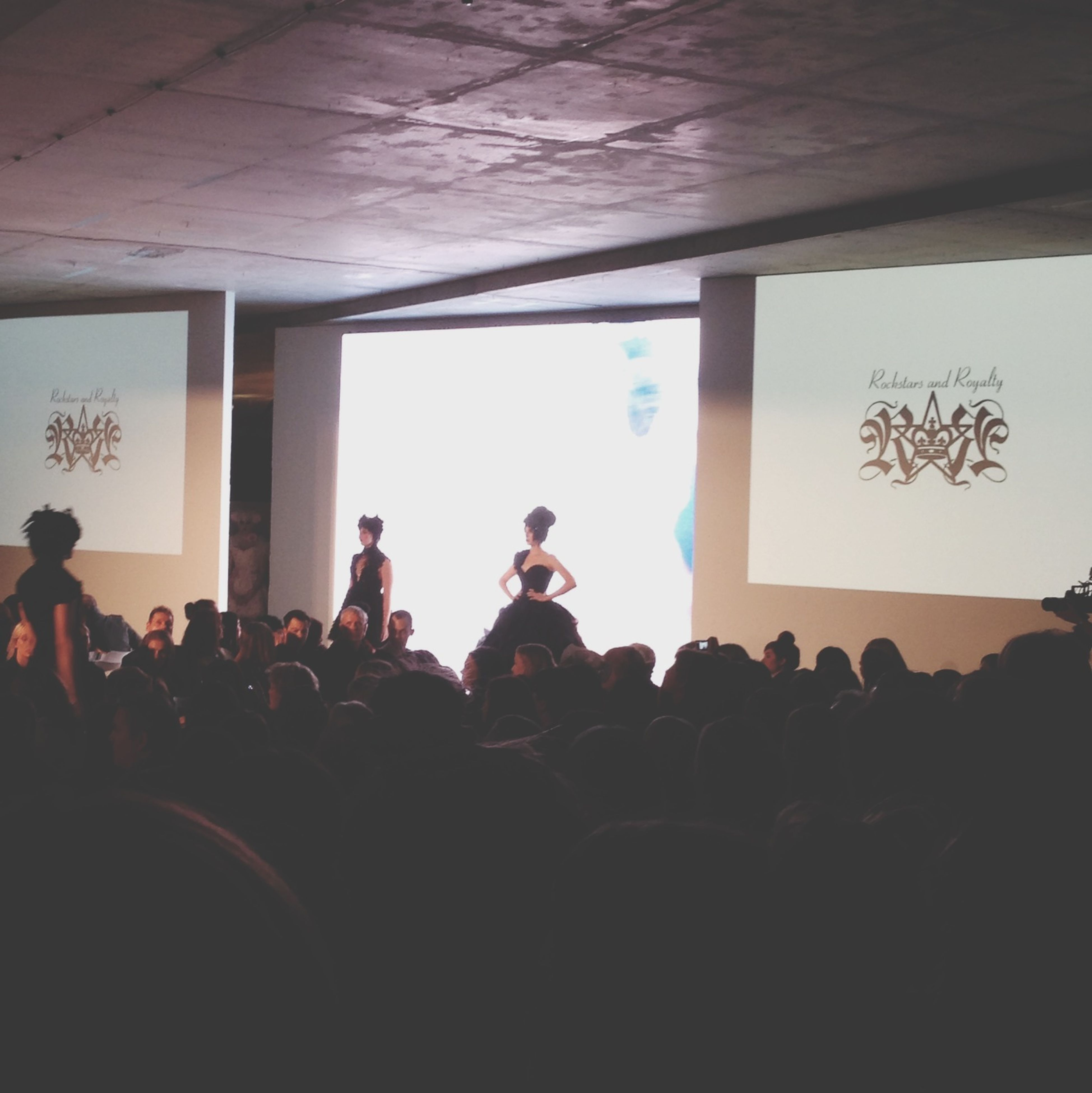 indoors, large group of people, silhouette, men, lifestyles, person, leisure activity, crowd, dark, togetherness, standing, window, copy space, built structure, arts culture and entertainment, sitting, architecture, illuminated, group of people