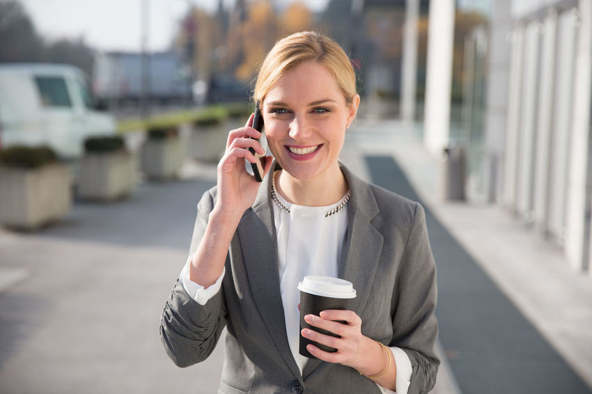 Successful young business woman using mobile technology while having a coffee break. Answering Coffee - Drink Coffee Cup Communication Connection Day Disposable Cup Drink Focus On Foreground Front View Holding Listening Mobile Phone One Person One Woman Only Outdoors Portability Portable Information Device Smart Phone Smiling Talking Technology Telephone Using Phone Wireless Technology