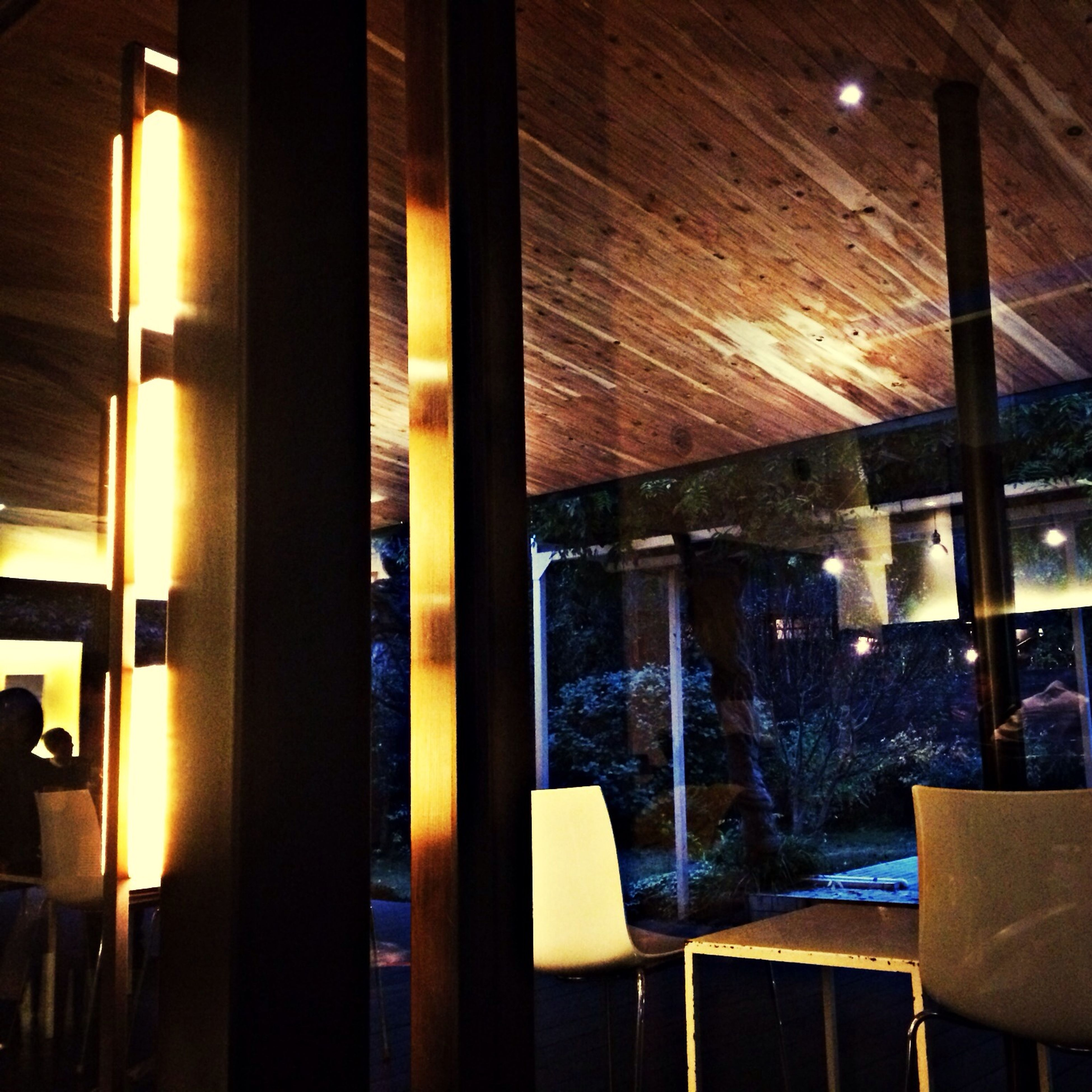 indoors, illuminated, lighting equipment, window, architecture, chair, home interior, interior, ceiling, built structure, absence, glass - material, light - natural phenomenon, restaurant, table, glowing, night, room, empty, architectural column