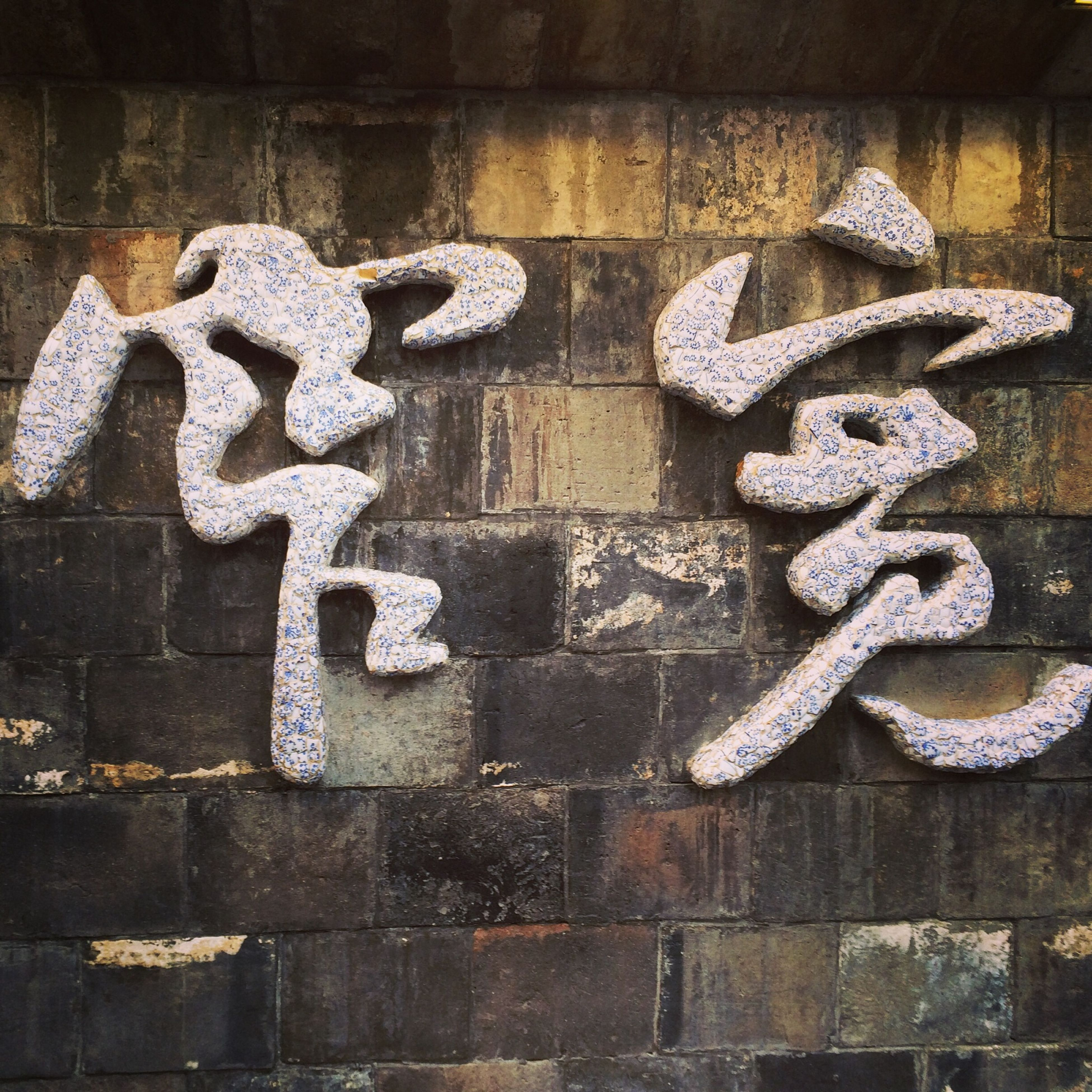 wall - building feature, art, art and craft, creativity, text, graffiti, human representation, communication, western script, wall, close-up, indoors, built structure, architecture, brick wall, no people, textured, animal representation, capital letter