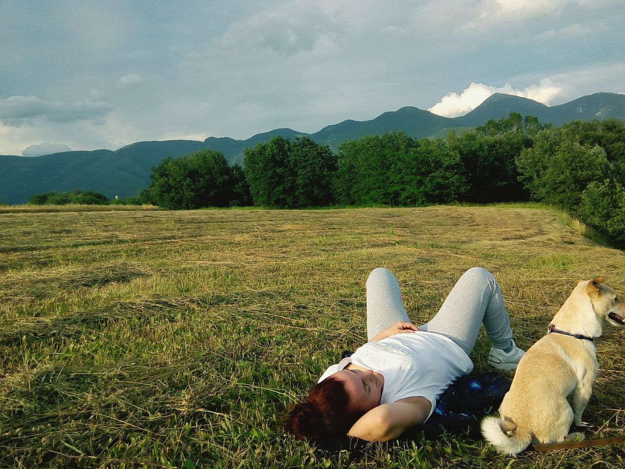 lying down, real people, mountain, tree, sky, grass, relaxation, day, field, sleeping, one person, casual clothing, nature, outdoors, growth, landscape, cloud - sky, full length, scenics, hands behind head, young women, young adult, beauty in nature, people