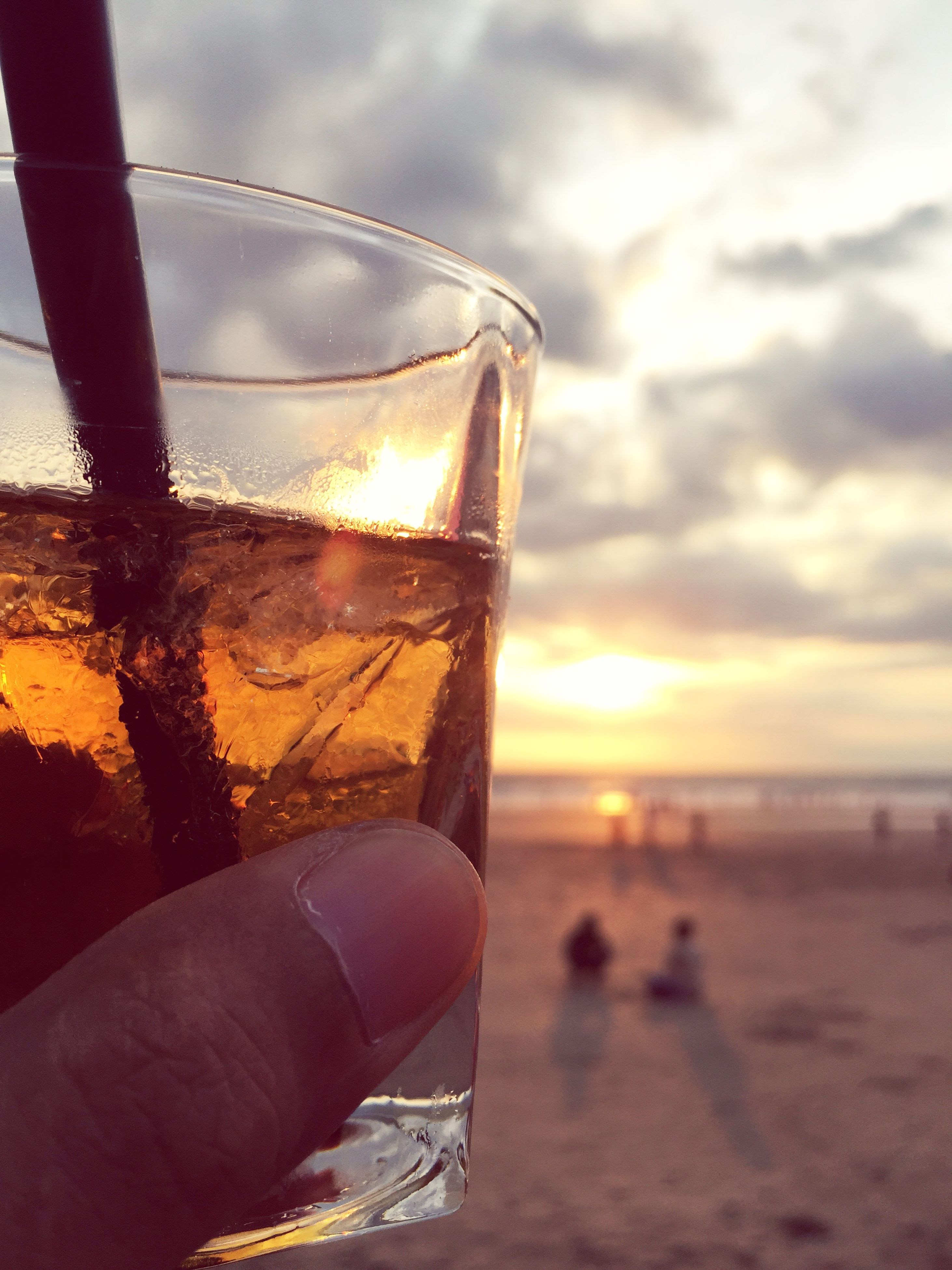 sunset, beach, sky, sea, focus on foreground, close-up, orange color, horizon over water, sun, part of, water, drink, sunlight, cloud - sky, shore, beauty in nature, scenics, nature, outdoors, glass - material