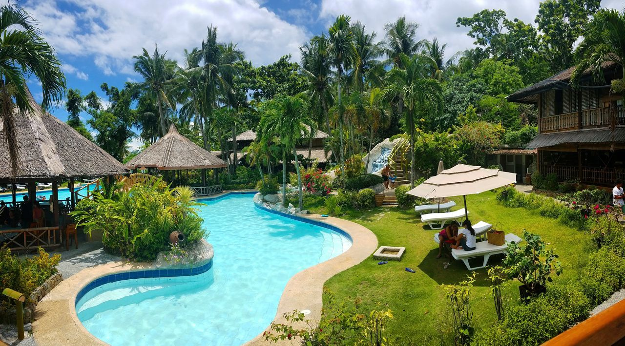 swimming pool, water, tourist resort, tree, luxury, architecture, palm tree, vacations, relaxation, day, sky, luxury hotel, outdoors, built structure, nature, building exterior, no people