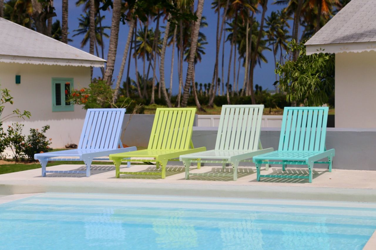 A set of four sun chairs at a pool in a Caribbean setting - wonderful! Pool Lifestyles Poolside Caribbean Pastel Colors Pastel Power Caribbean Life Sundeck Sunchair Summertime Summer Holidays Vacations Leisure Time Luxury Swimming Pool Palm Tree Relaxation Lounge Chair Deck Chair Vacations No People
